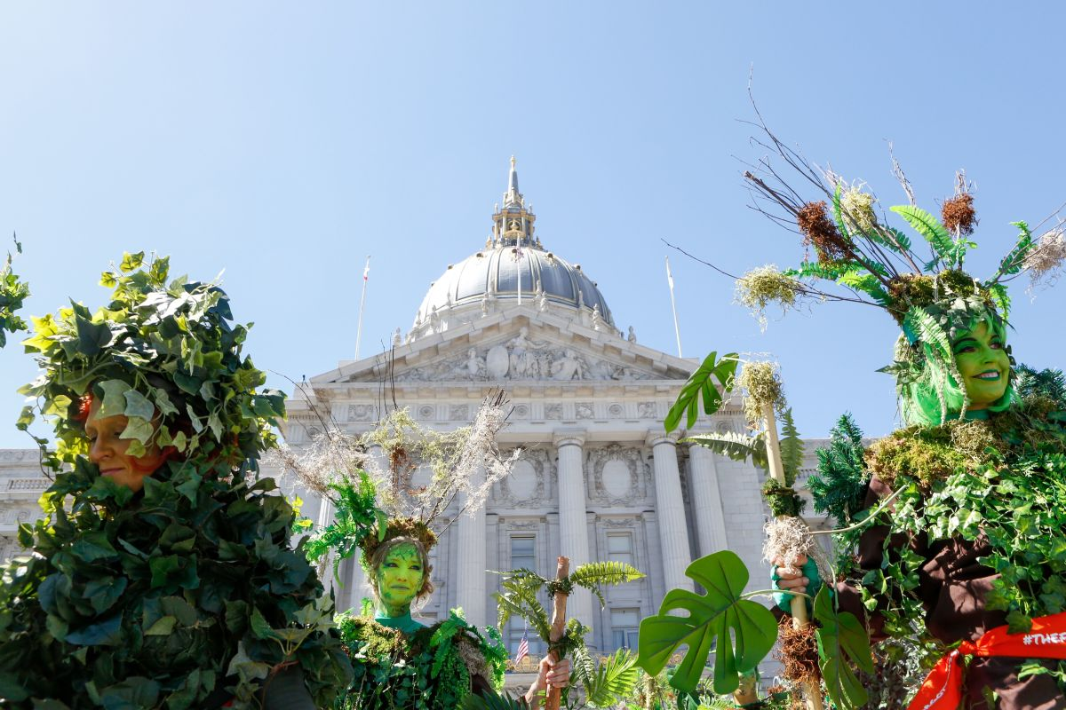 Women dressed as trees stand in front of San Francisco City Hall after marching in the Rise for Climate March on September 8th, 2018.