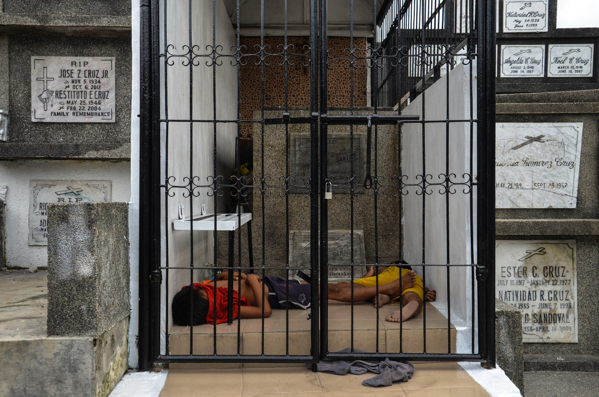 Two boys sleep in the heat of the day in a mausoleum, where their father is a caretaker, in Manila North Cemetery.