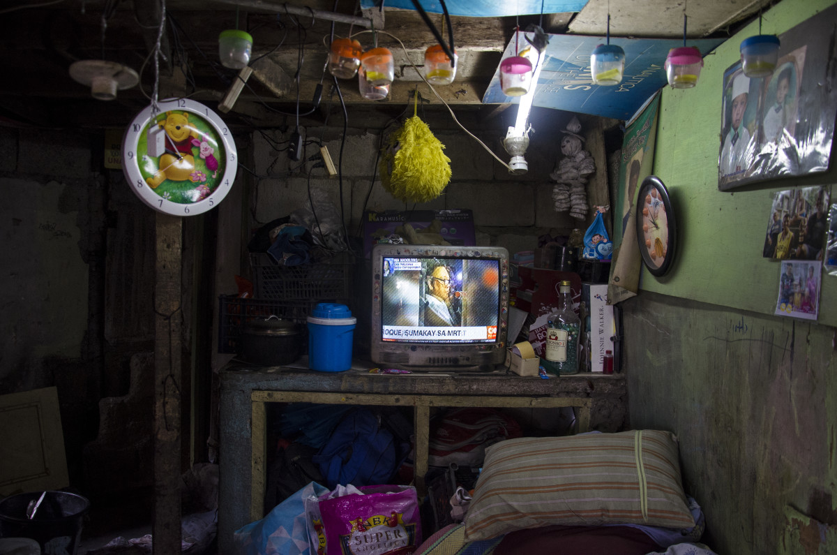 """Ricardo Medina, a caretaker in Pasay cemetery, found out his 24-year-old son, Ericardo, had been killed in an EJK after seeing him on the television with his head wrapped in packaging tape and a sign tied across his chest that read """"pusher."""""""