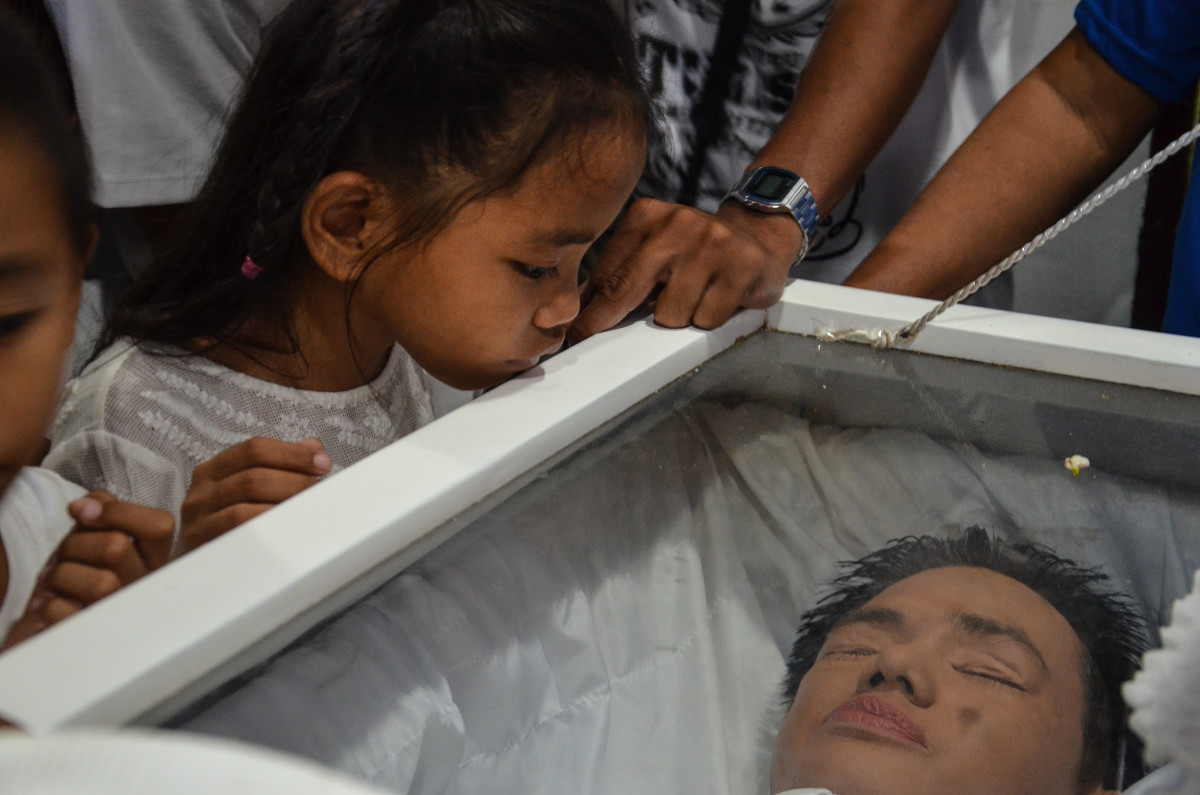 A family member looks at Enrico in his coffin at his funeral in Navotas.