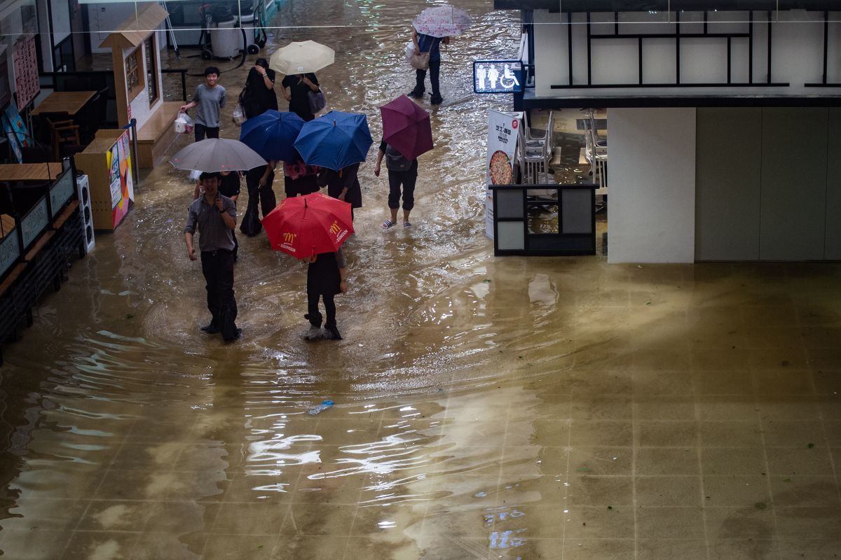 People walk through a flooded shopping mall in the Heng Fa Chuen district during Typhoon Mangkhut in Hong Kong, China, on September 16th, 2018.