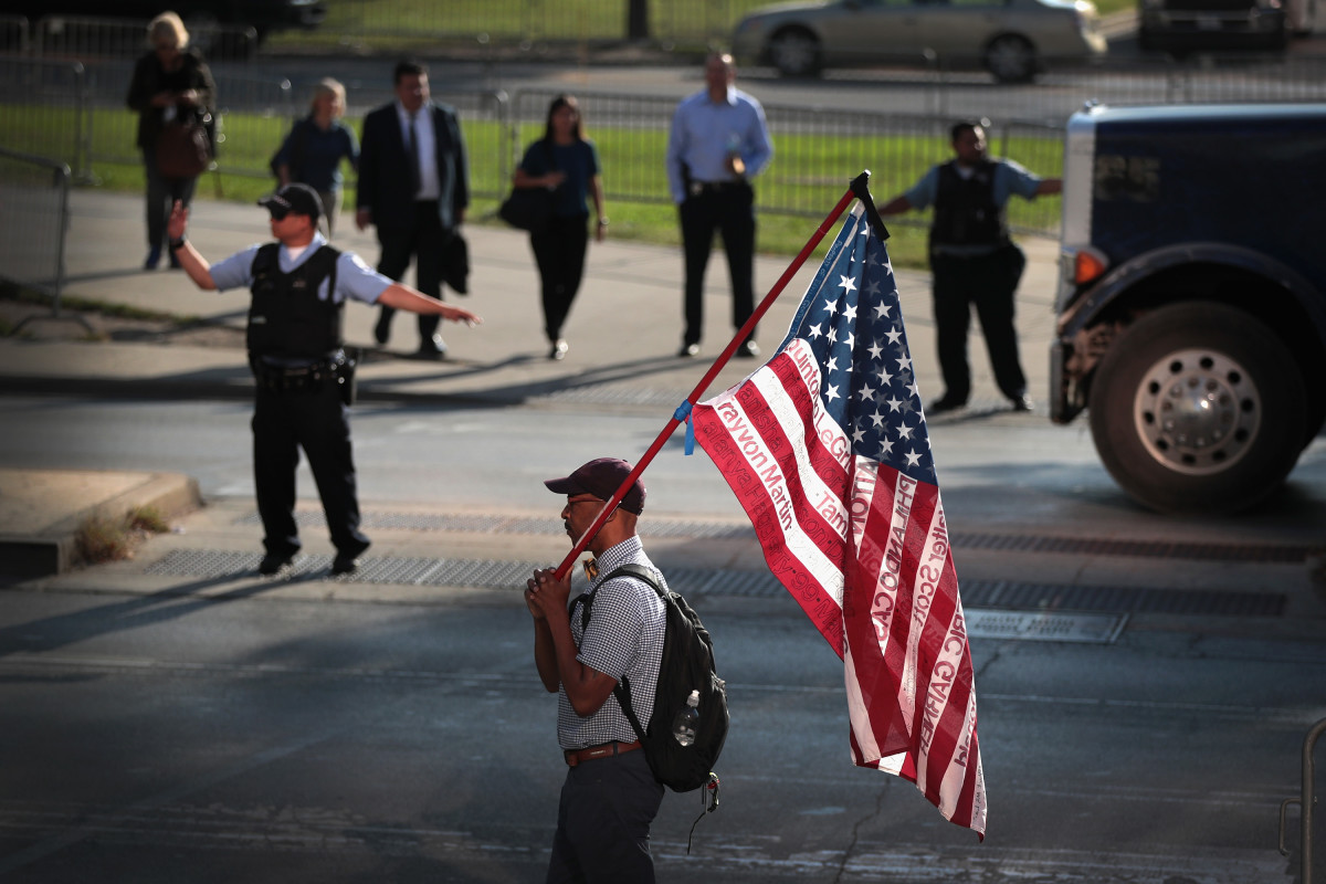 A demonstrator holds an American flag emblazoned with the names of victims who were fatally wounded by police officers during a protest outside the Leighton Criminal Courthouse Building on the first day of Chicago police officer Jason Van Dyke's murder trial on Monday, September 17th, 2018, in Chicago, Illinois. Van Dyke faces murder charges for shooting 17-year-old Laquan McDonald 16 times in an October of 2014 confrontation.