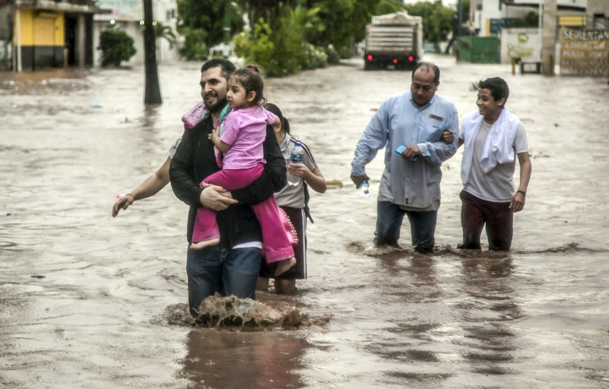 People wade through a flooded street in the city of Culiacán, in Sinaloa State, Mexico, on September 20th, 2018. Heavy rains flooded many of Culiacán's neighborhoods in just a few hours.