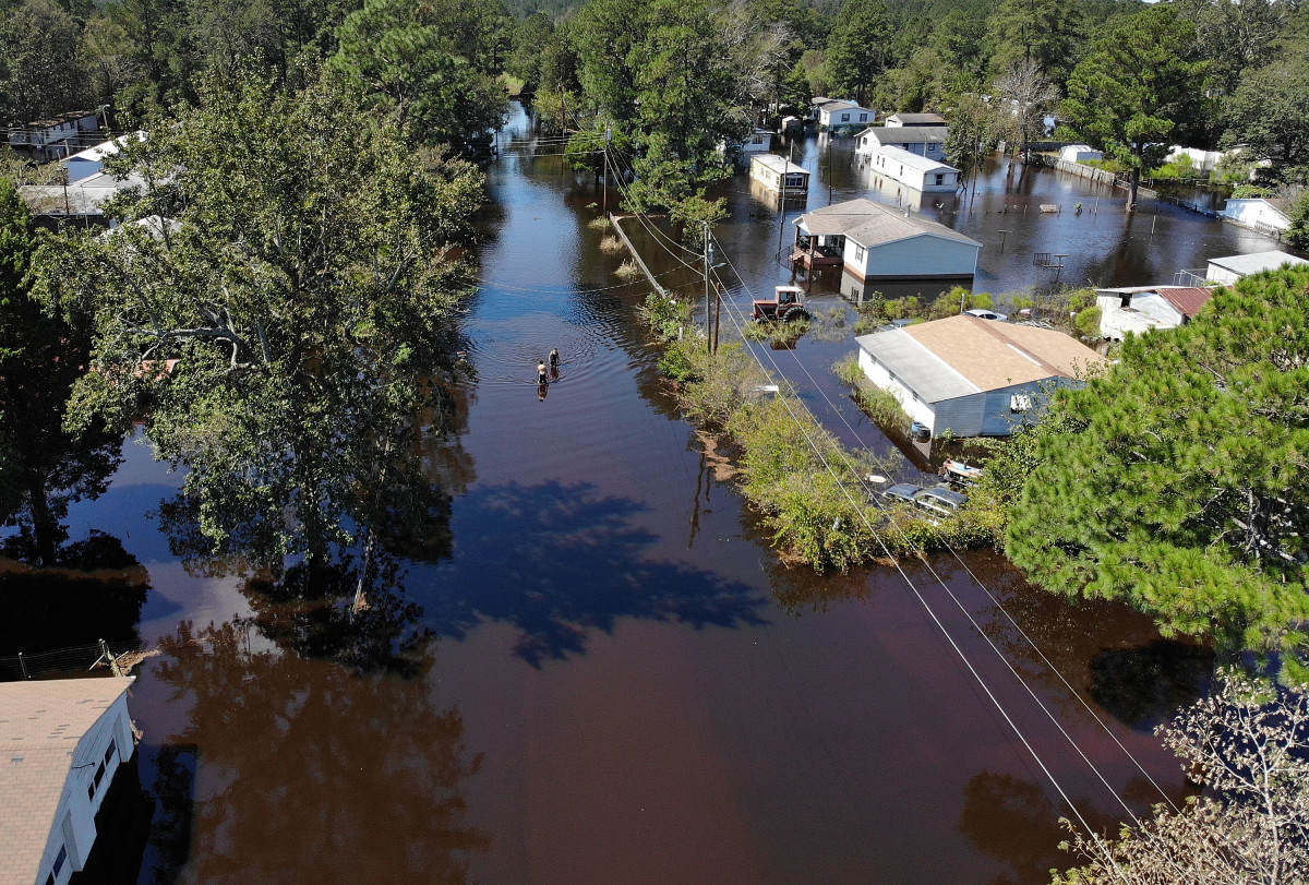 People walk through a flooded neighborhood after heavy rains brought on by Hurricane Florence on September 19th, 2018, in Lumberton, North Carolina.