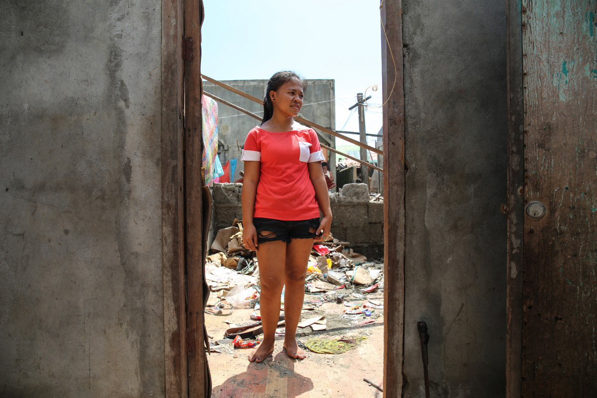"Sasana Raquini, 18, stands in her home in Aparri, which lost both its walls and roof. Today, she is cleaning up alone as her father and brother are out fishing. ""I am hopeful that the government will help,"" she says."