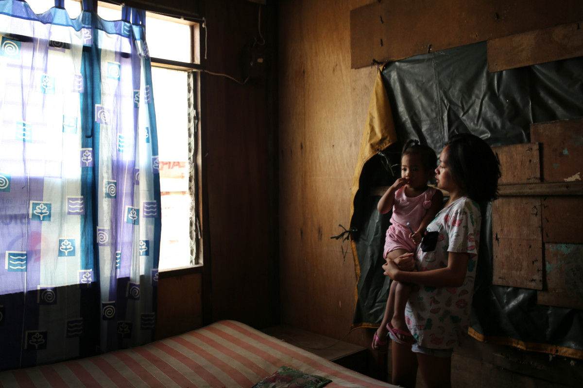 "Sira Alfonso, 20, and one-year-old Carolyn Joy were in their house with seven family members when the typhoon hit. ""This is the second Typhoon to damage our walls and ceiling. Can you smell that, damp? The water is locked in the walls now,"" Sira says."