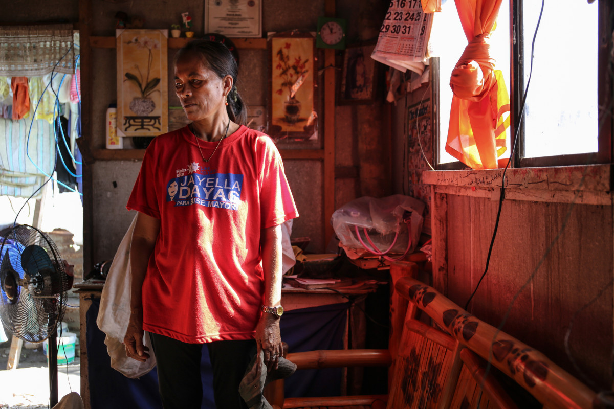 "Rowana Basilio, 46, stands inside her home in Aparri. ""The roof was taken by the typhoon but the pigs survived,"" she says, gesturing toward the three pigs in her backyard."