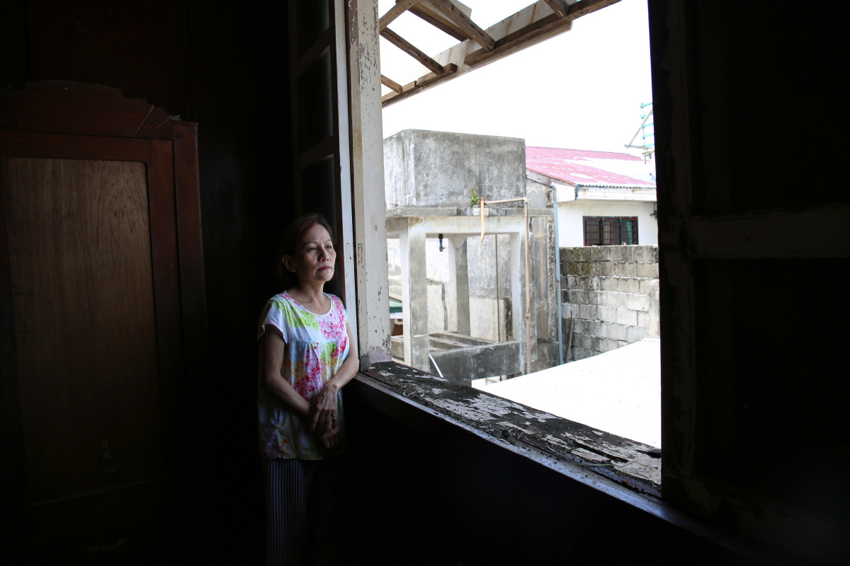 """Vicky Romillio Verzoso, 58, stands in her bedroom. """"The typhoon ripped the roof off and blew out the glass windows,"""" she says."""