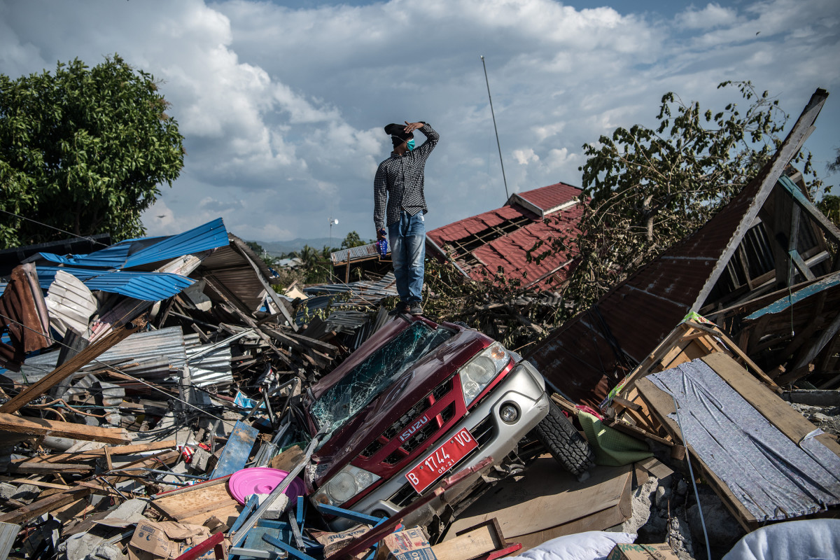 A man stands on a destroyed car as he views the rubble and debris of destroyed buildings following an earthquake, on October 2nd, 2018, in Palu, Indonesia.