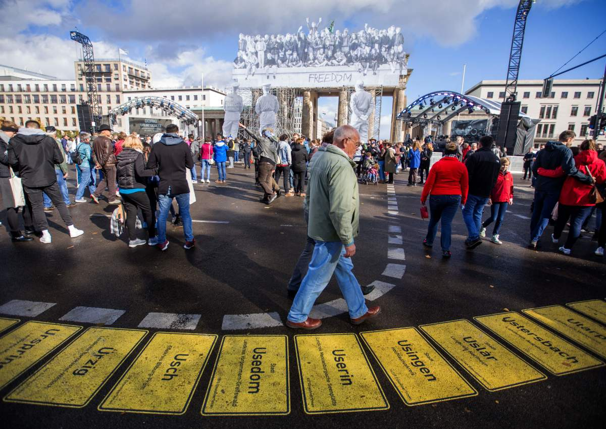 People walk in front of the Brandenburg Gate, decorated with a photo collage by the French street artist and photographer known as JR for German Unity Day, on October 3rd, 2018, in Berlin, Germany. The national holiday celebrates the reunification of East and West Germany in 1990.