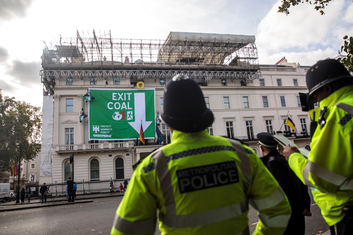 Police officers look on as Greenpeace activists hang from ropes after unfurling a banner outside the German embassy in a protest against coal on October 8th, 2018, in London, England. The stunt by the environmental campaign group came on the day that a report was released by the United Nations' top climate science panel calling for accelerated action to tackle climate change.