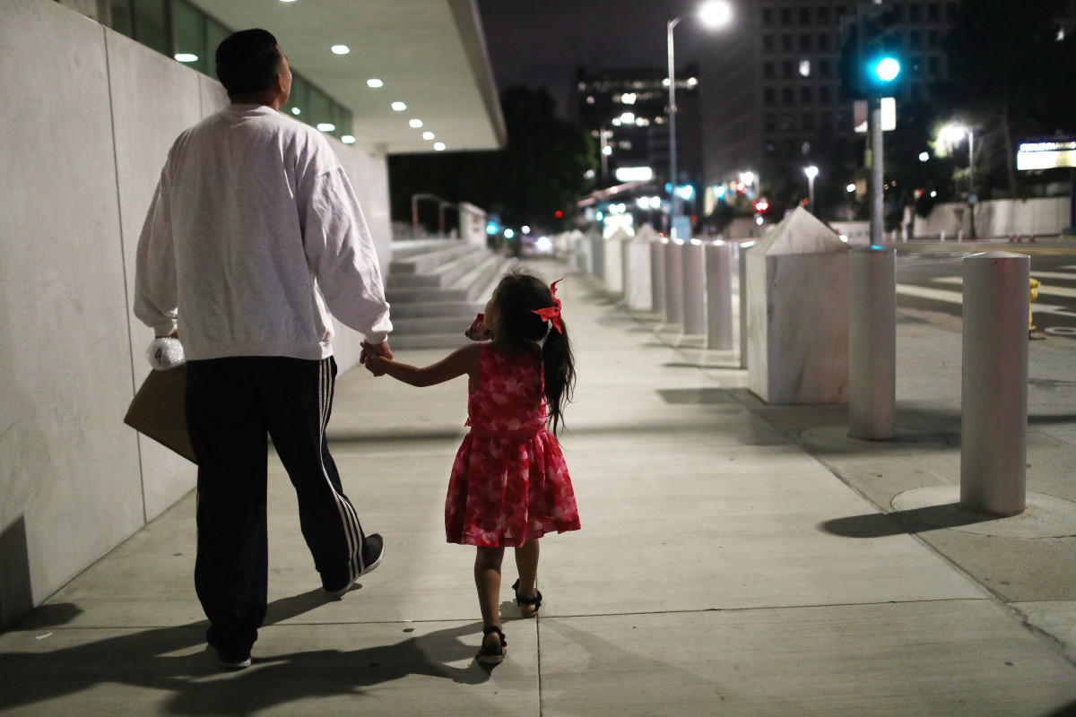 A Honduran man walks with his daughter near Metropolitan Detention Center on October 2nd, 2018, in Los Angeles, California.
