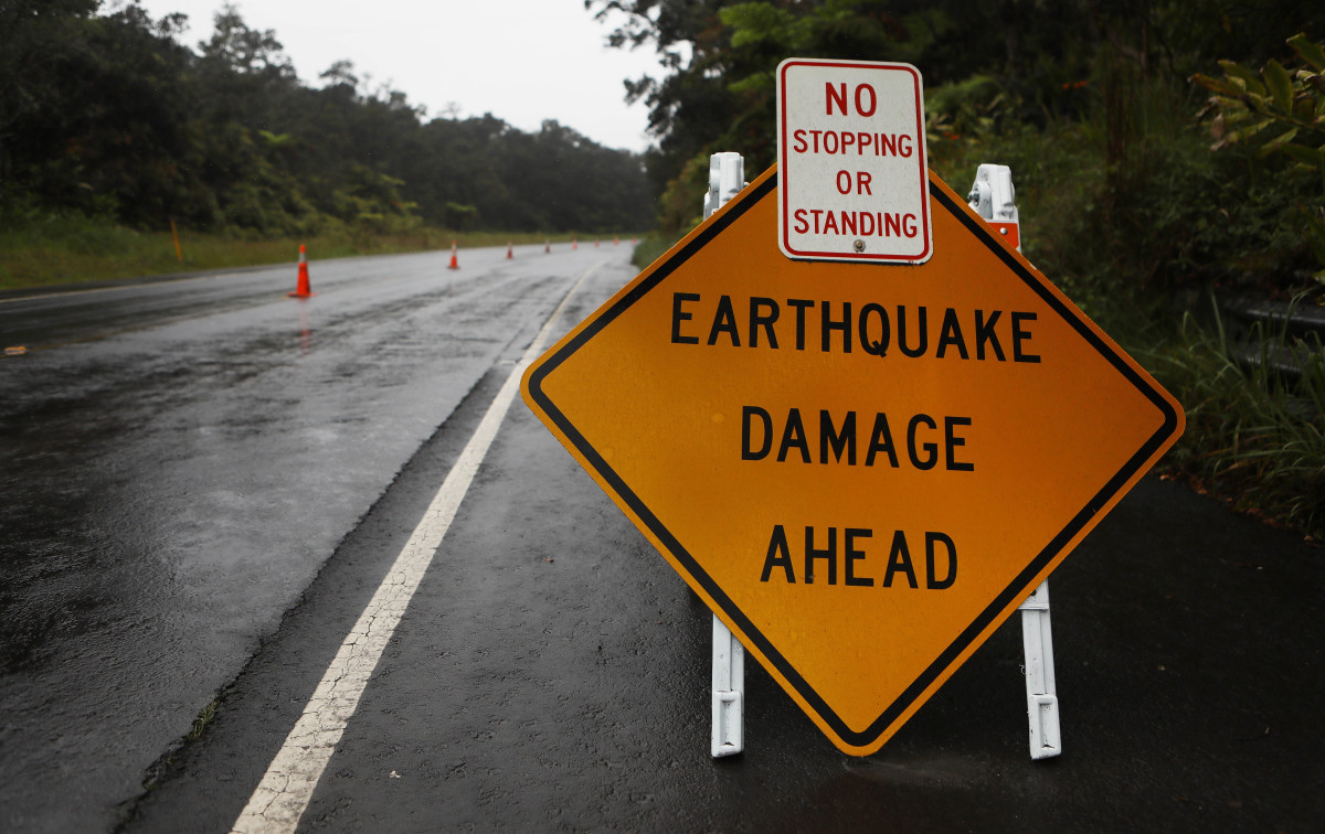 A sign is posted warning of earthquake damage to the road from seismic activity at the Kilauea volcano on Hawaii's Big Island on May 17th, 2018, in Hawaii Volcanoes National Park, Hawaii.