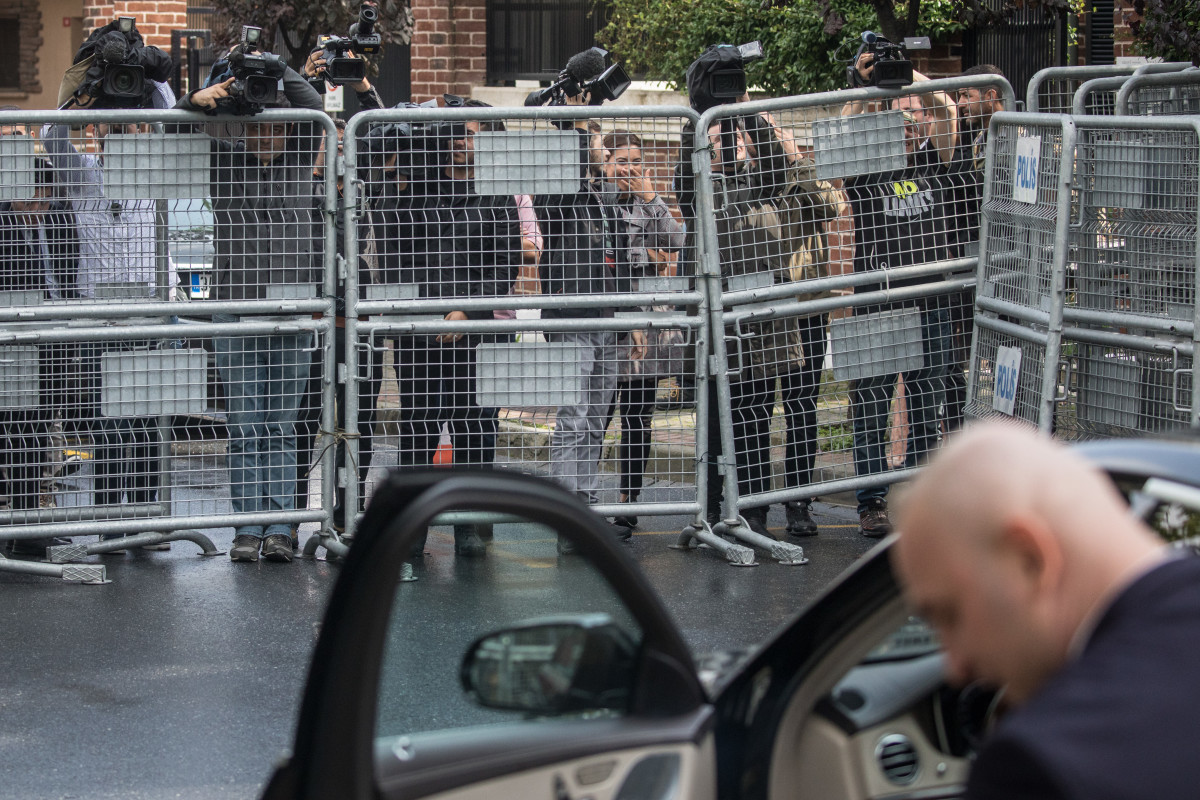 Members of the press film over a police barricade as a driver waits to take a passenger from the entrance of Saudi Arabia's consulate on October 11th, 2018, in Istanbul, Turkey.