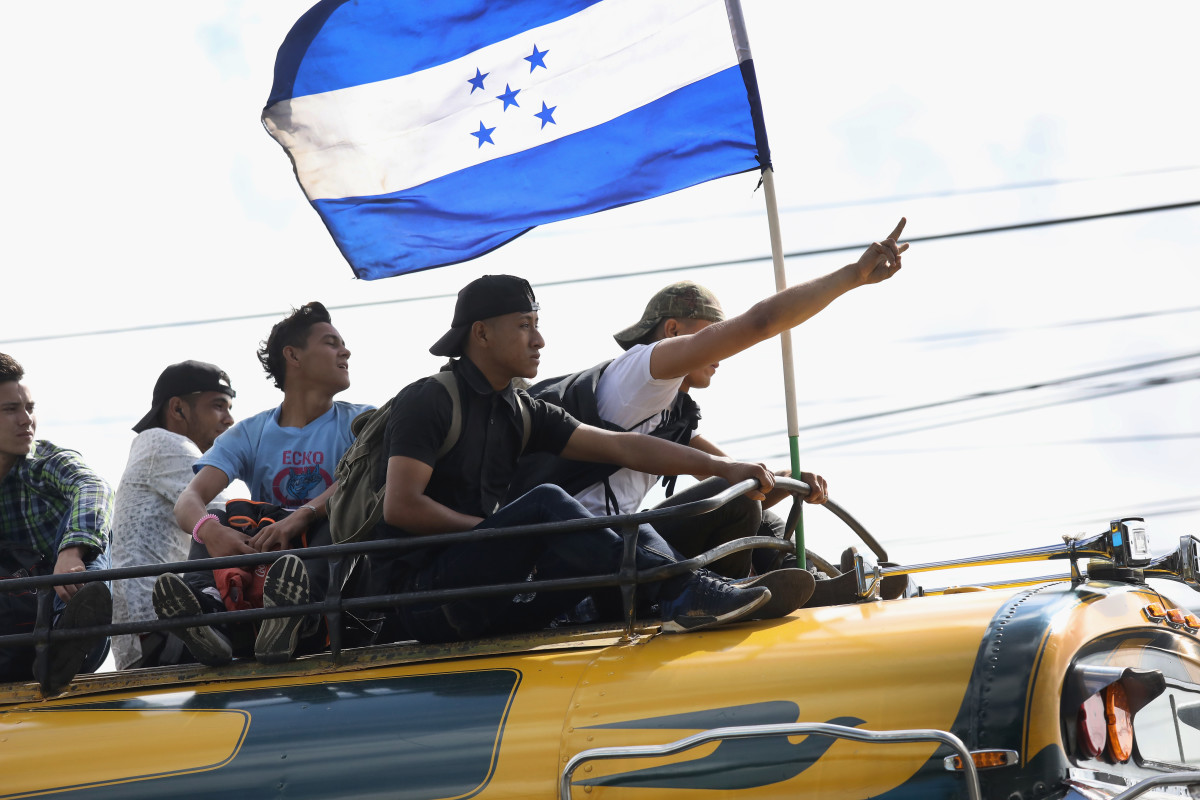Migrants carry the flag of Honduras while on a caravan of immigrants en route to the Mexican border on October 18th, 2018, in Guatemala City, Guatemala. The caravan of thousands of Central Americans, most from Honduras, hopes to eventually reach the United States. U.S. President Donald Trump has threatened to cancel the recent trade deal with Mexico and withhold aid to Central American countries if the caravan isn't stopped before reaching the U.S.