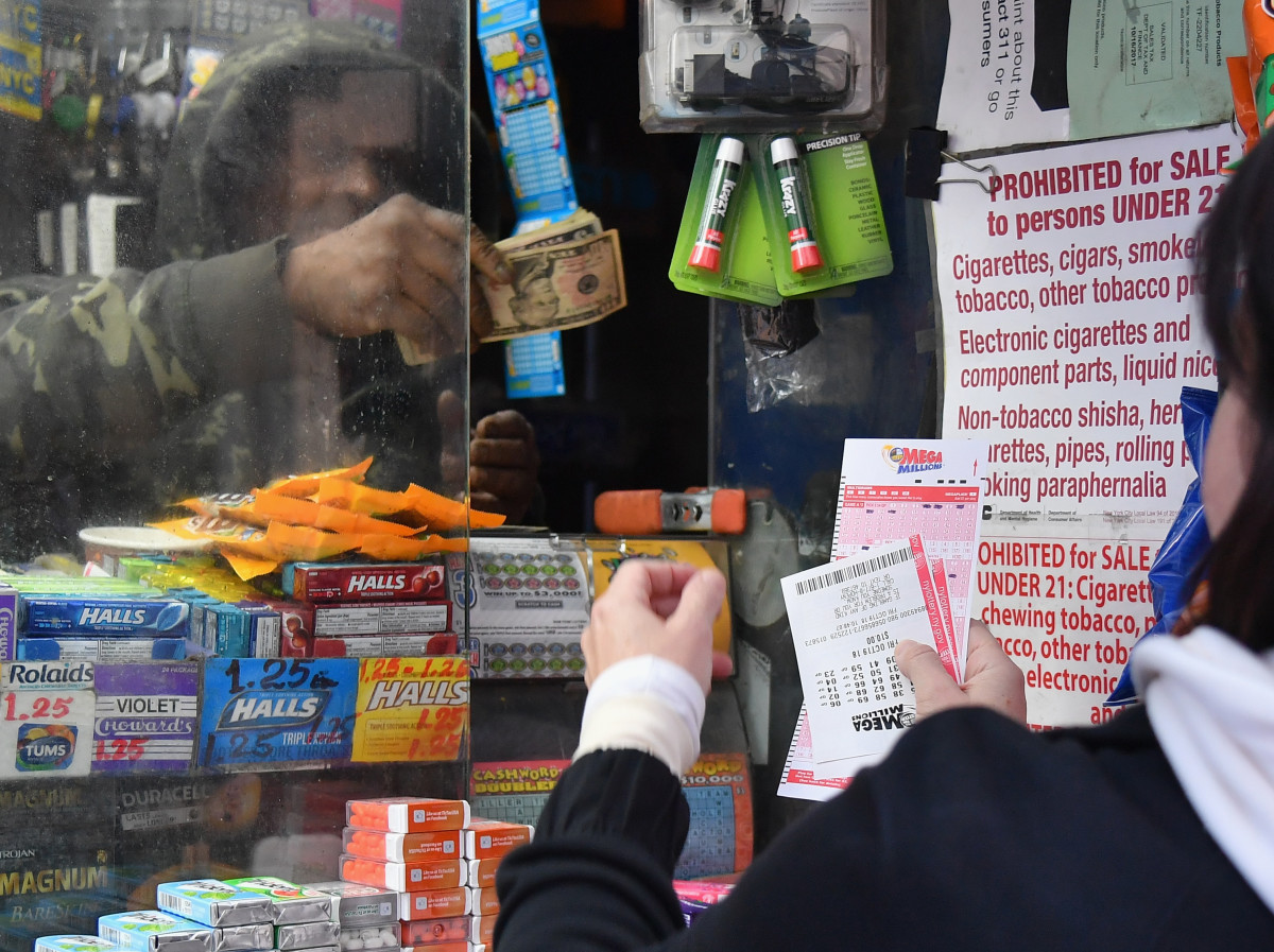 A woman purchases Mega Millions lottery tickets on October 19th, 2018, in New York City. The Mega Millions jackpot is currently up to $970 million.
