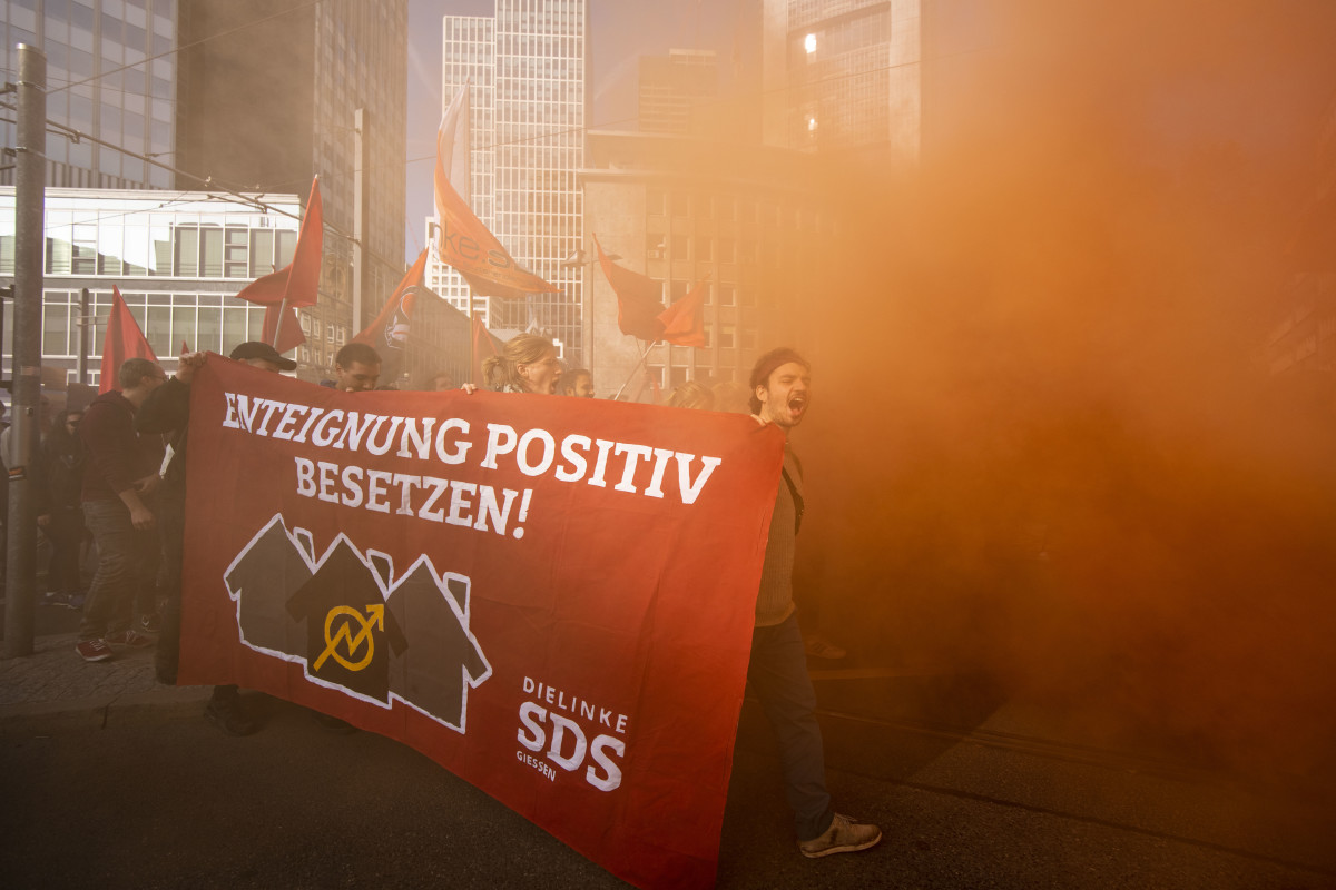 Protesters walk in the smoke while demonstrating against rising housing rental prices on October 20th, 2018, in Frankfurt, Germany. Skyrocketing costs for housing have become a major issue in cities across Germany, with local government scrambling to find policy solutions. Frankfurt in particular is already attracting wealthy newcomers as the city becomes an alternative for companies in the financial sphere relocating from Brexit-afflicted London. In other cities, especially Berlin, foreign investors, including from China, are parking their money in luxury apartment purchases.