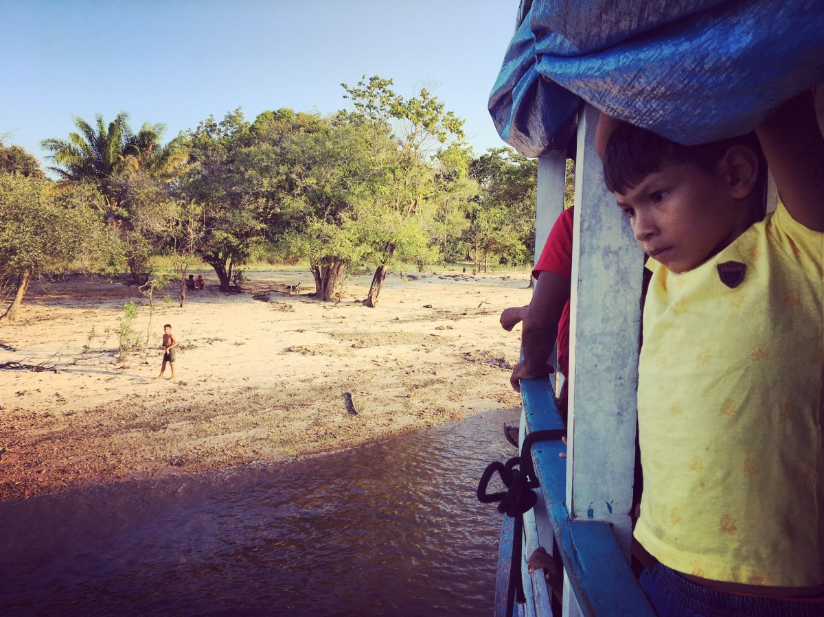 A little boy looks out during one of the stops the Michael made along our route between Santarem and São Pedro.