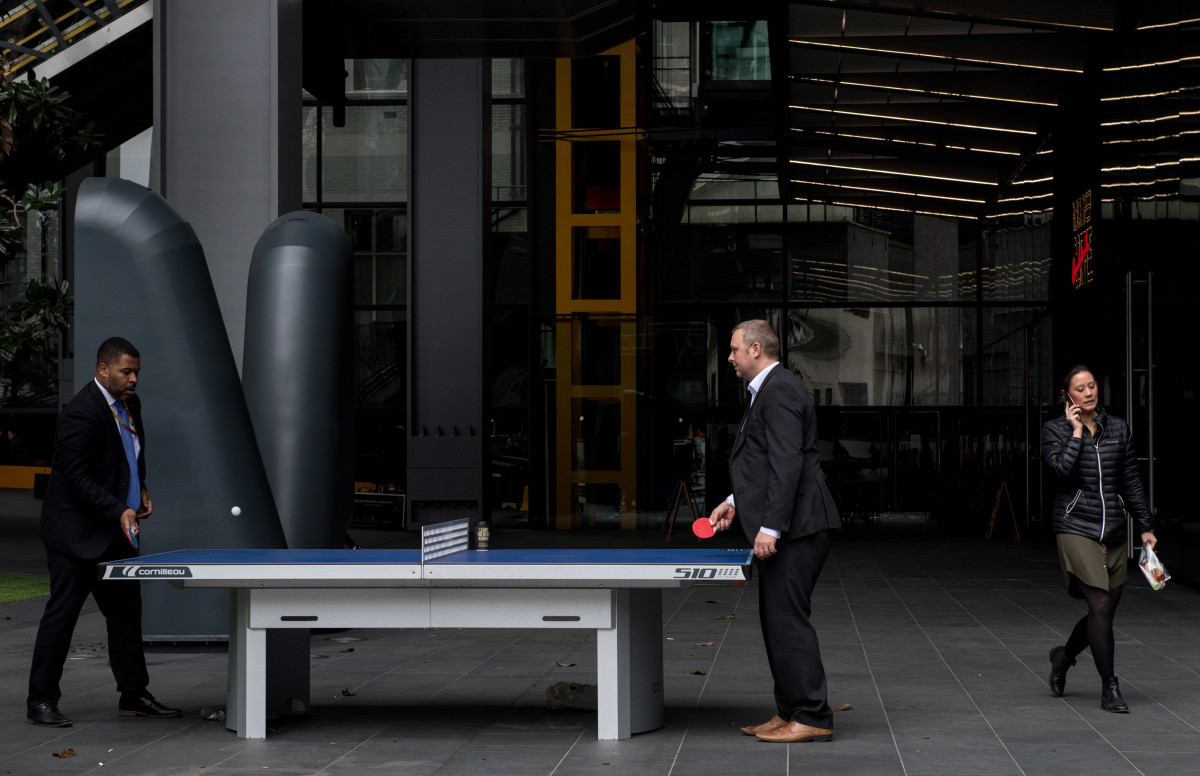 A woman walks past two men playing table tennis outside the Leadenhall Building as the deadline nears for companies to report their gender pay gap on April 4th, 2018, in London, England.