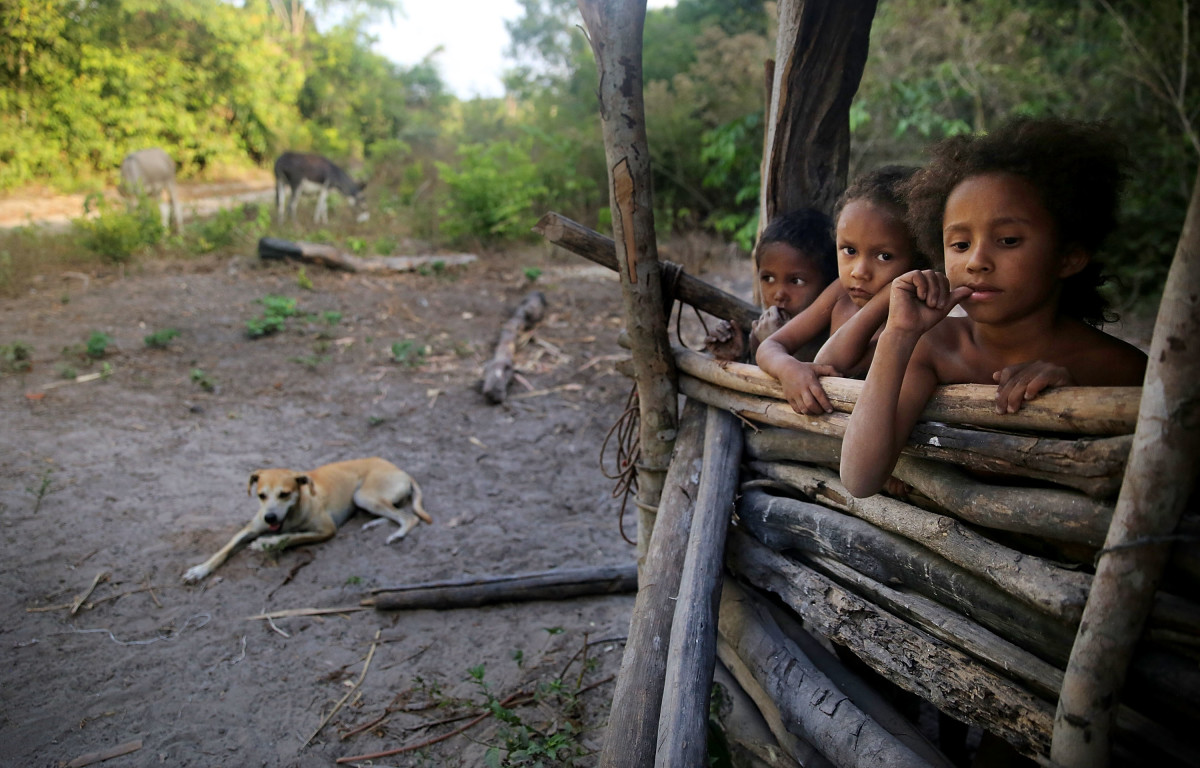 Young members of the Serra family gather in the building where family members make traditional farinha near their home in the Imbiral quilombo, which community members say is being heavily encroached upon by illegal logging and cattle ranching.