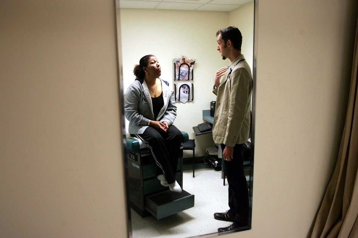 Dr. Ethan Brackett listens during an examination of patient Cristina Valdez at the Codman Square Health Center on April 11th, 2006, in Dorchester, Massachusetts.