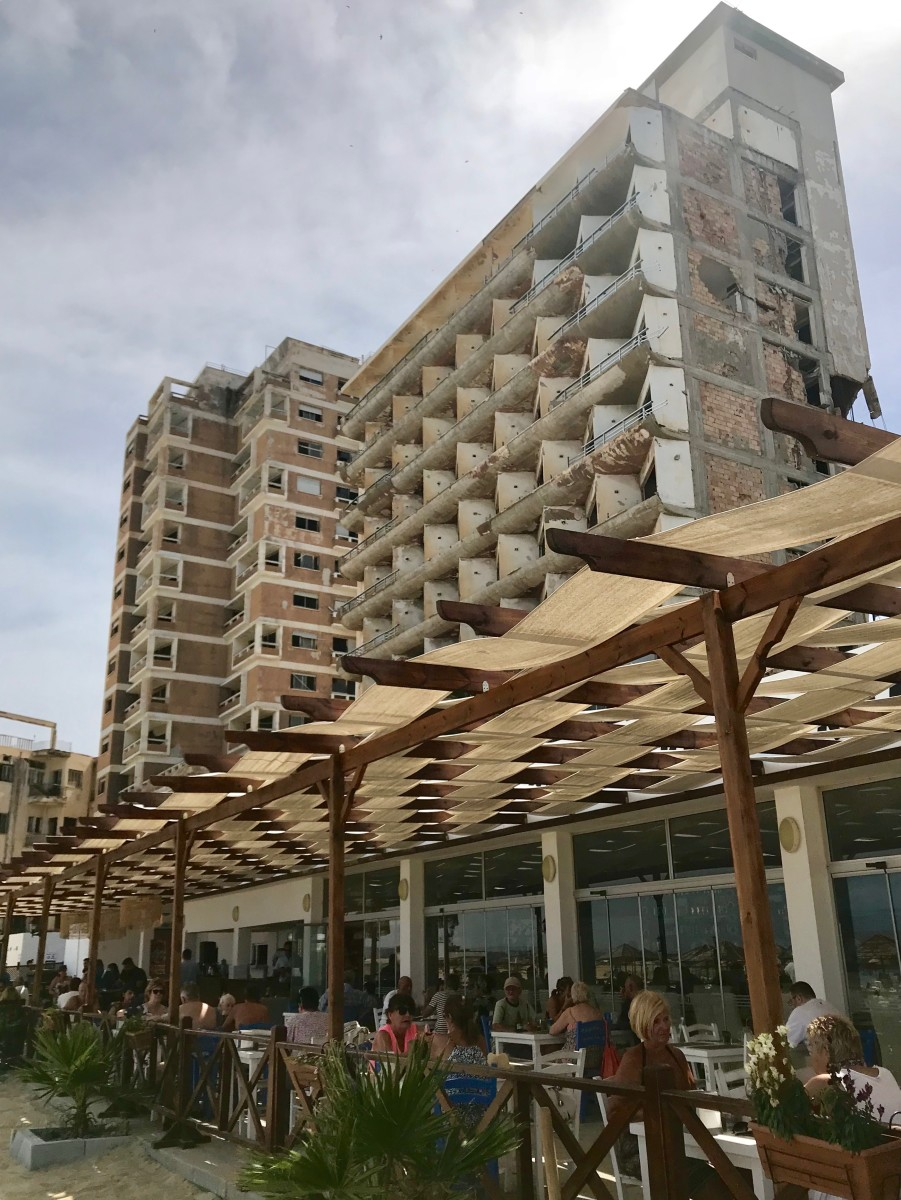 A trendy café in Famagusta with crumbling buildings in the background.