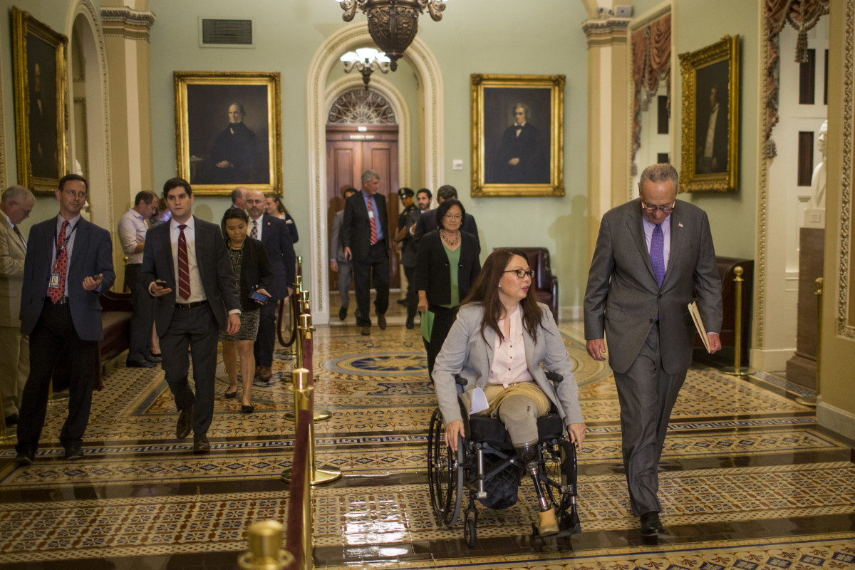 Senator Tammy Duckworth and Senate Minority Leader Chuck Schumer head to a weekly news conference on Capitol Hill in Washington, D.C., on August 21st, 2018.
