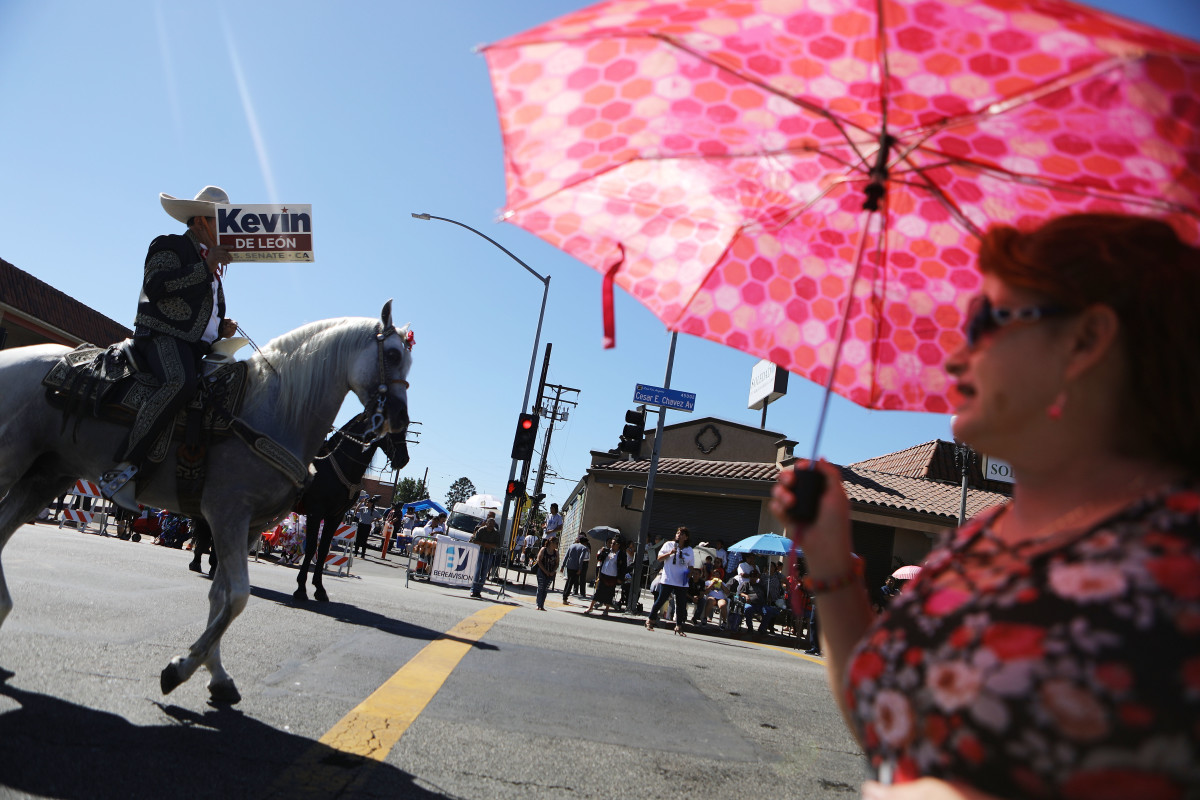 A horseback rider carries a sign in support of Kevin de León during the East L.A. Mexican Independence Day Parade on September 16th, 2018, in Los Angeles, California.