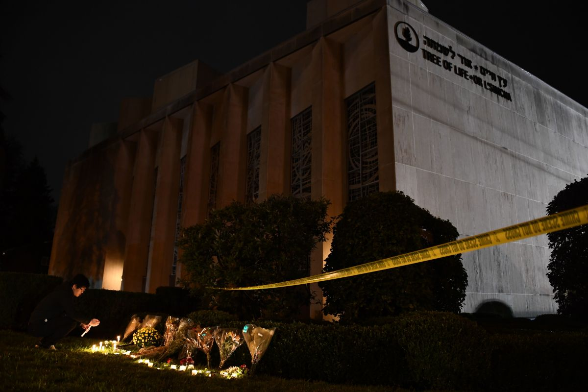 A man kneels to light a candle beneath police tape outside the Tree of Life Synagogue after a shooting there left 11 people dead in the Squirrel Hill neighborhood of Pittsburgh on October 27th, 2018. A heavily armed gunman opened fire during a baby-naming ceremony at the synagogue in Pittsburgh's Squirrel Hill neighborhood in the deadliest anti-Semitic attack in recent American history.