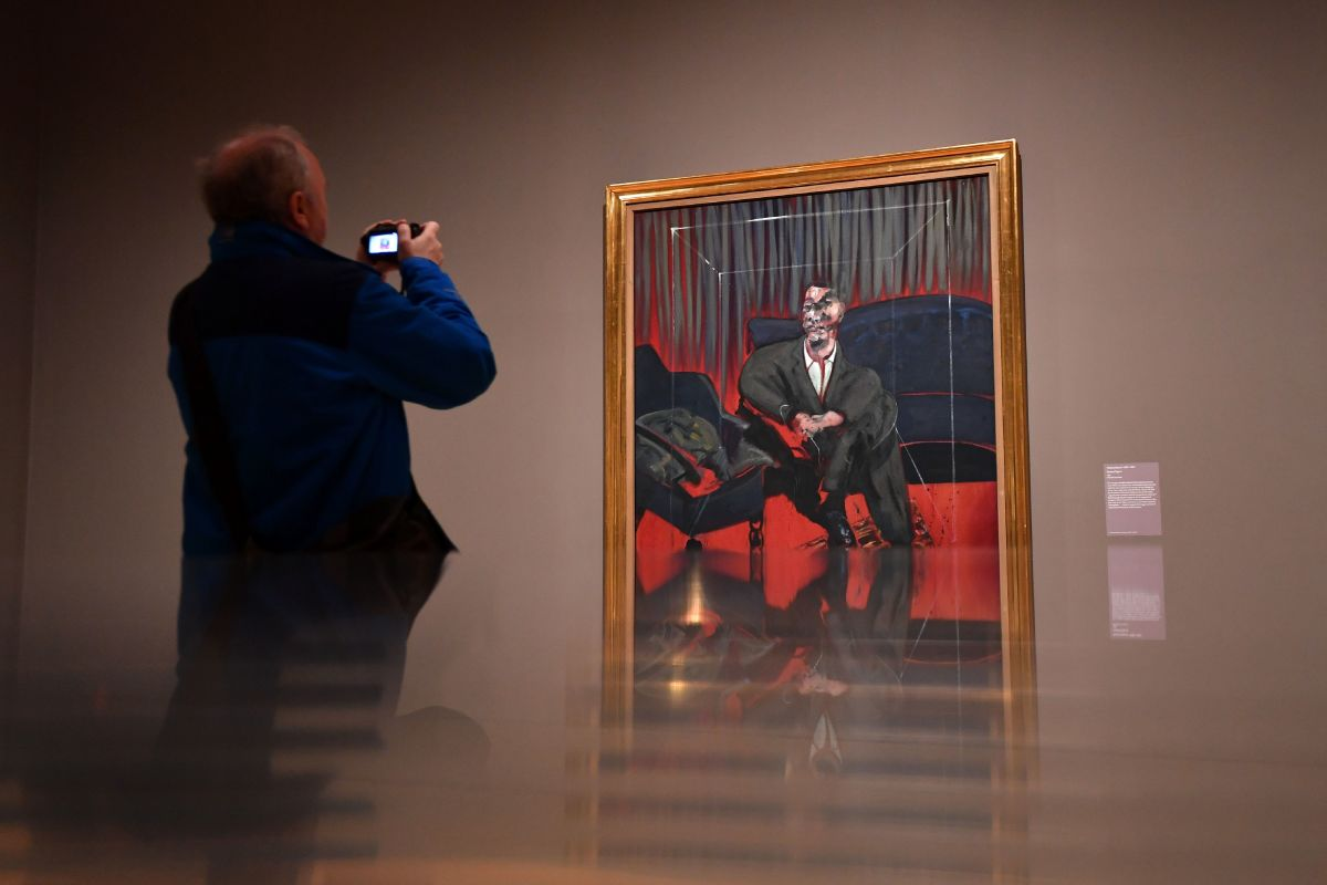 A man takes a photograph of Seated Figure, 1961, an oil painting by Irish-born British artist Francis Bacon, as part of the Queer British Art 1861-1967 exhibition at the Tate Britain in London on April 3rd, 2017.