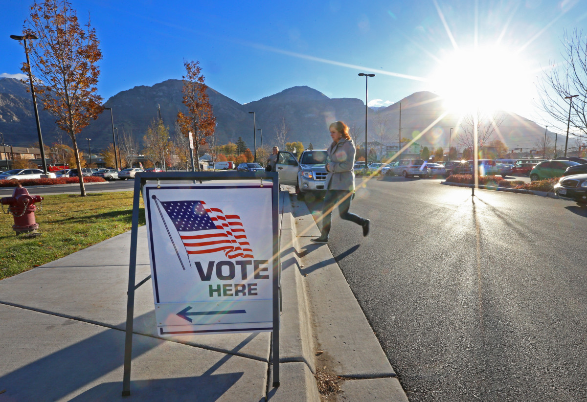 A woman walks into a polling center to vote in the mid-term elections as the morning sun rises over the Utah Wasatch Mountains on November 6th, 2018, in Provo, Utah.