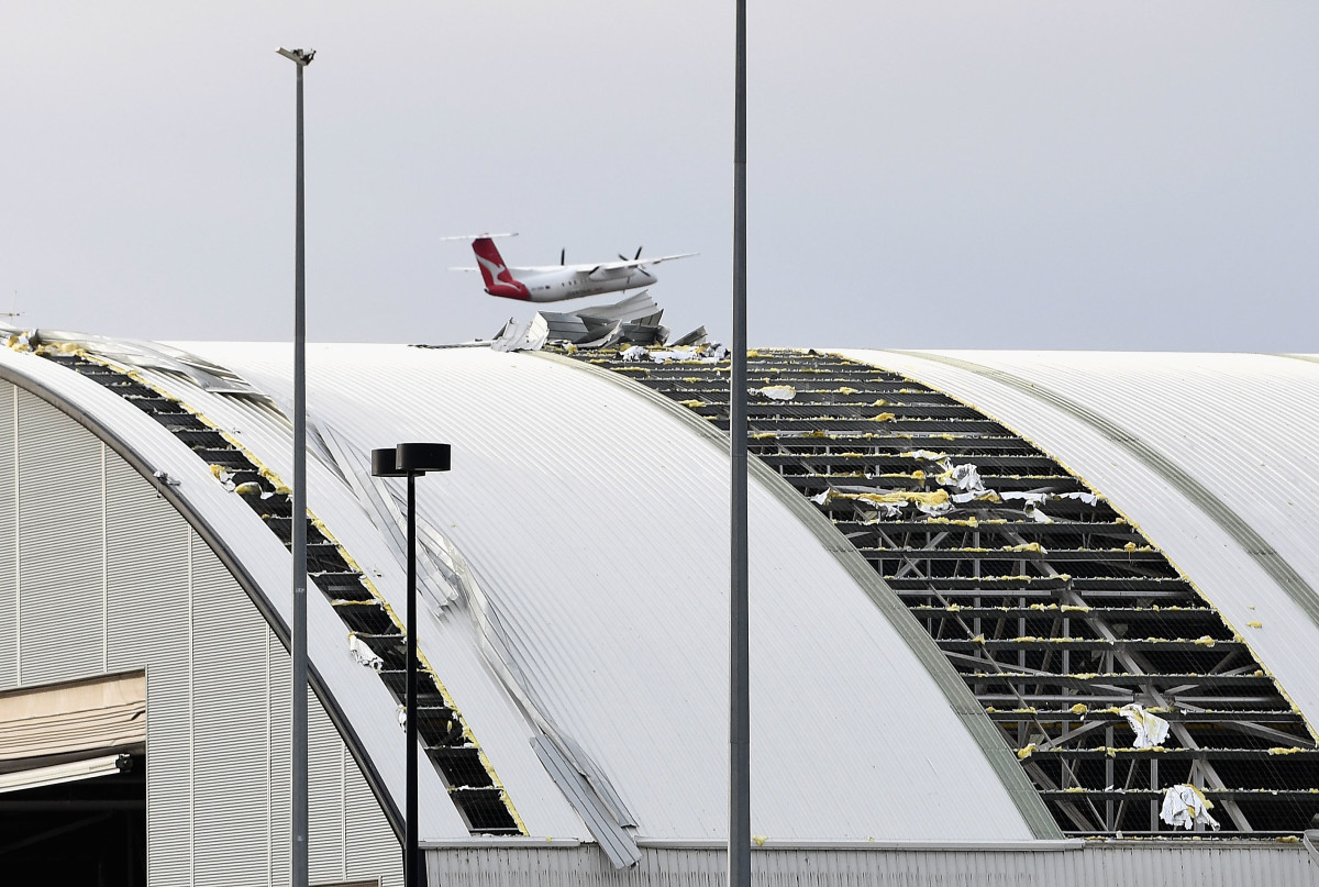 A plane flies over a damaged airport hangar roof that was ripped off in the storm that hit Canberra, Australia, on November 2nd, 2018. Strong winds and a thunderstorm swept through the state late in the afternoon.