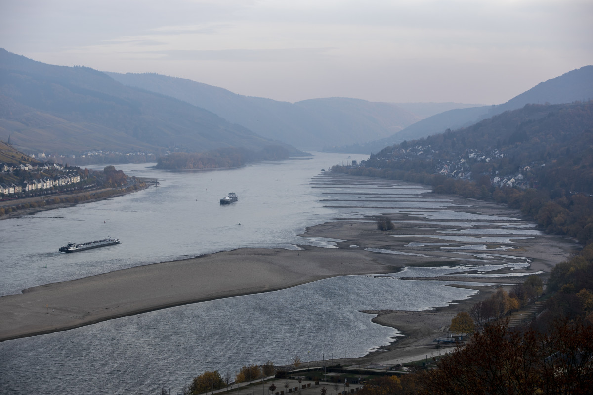 Cargo ships maneuver near the banks of the Rhine River on November 9th, 2018, near Kaub in Germany. The summer heat wave in Germany, unfavorable wind conditions, and no rain left the Rhine—which begins in the Swiss Alps, runs through Germany, and empties into the North Sea—at record low water levels. This created problems in the shipping industry, brought environmental damage, caused oil prices to rise, and meant billions of euros of losses. Although rainfall is expected soon, experts warn it will probably take weeks or months to bring water levels in the river, Germany's most important waterway and a key shipping route for the Netherlands and France, back to normal.