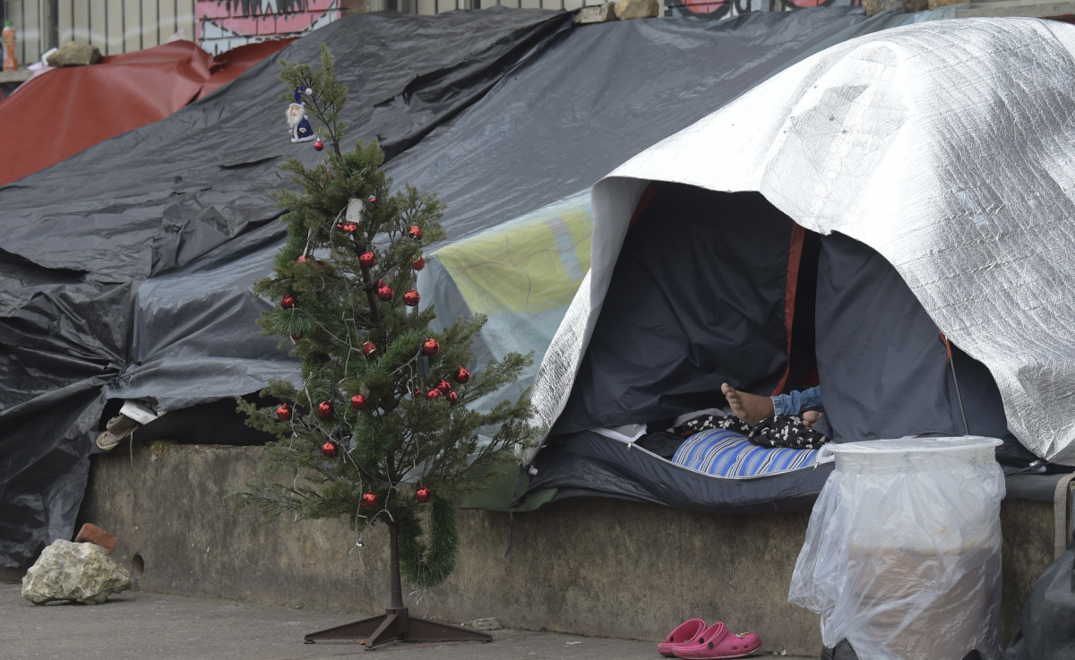 A Venezuelan migrant rests next to a Christmas tree at an improvised camp near a bus terminal in Bogota, Colombia, on November 9th, 2018.