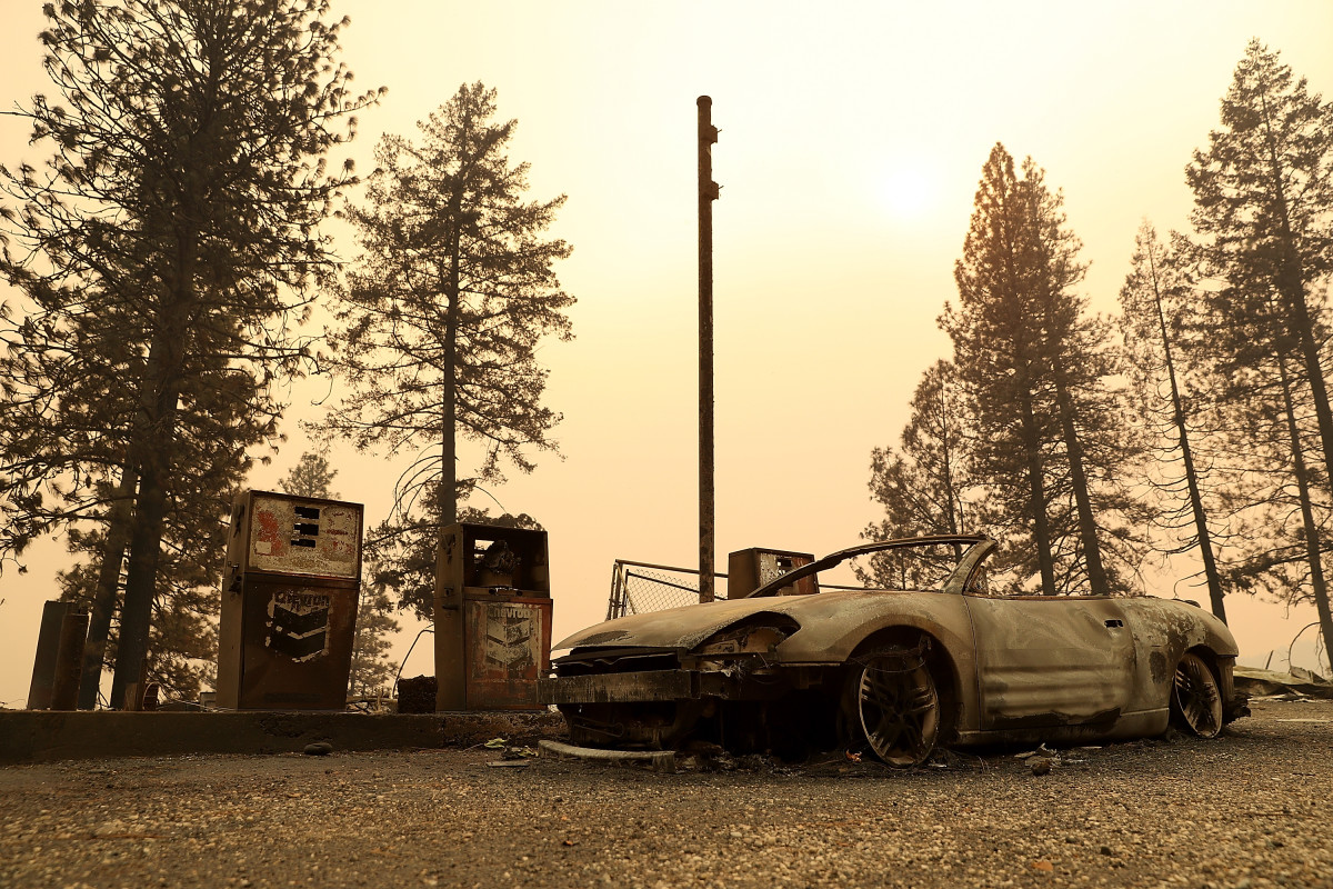 A burned out car sits next gas pumps at a gas station that was destroyed by the Camp Fire on November 11th, 2018, near Parkhill, California.