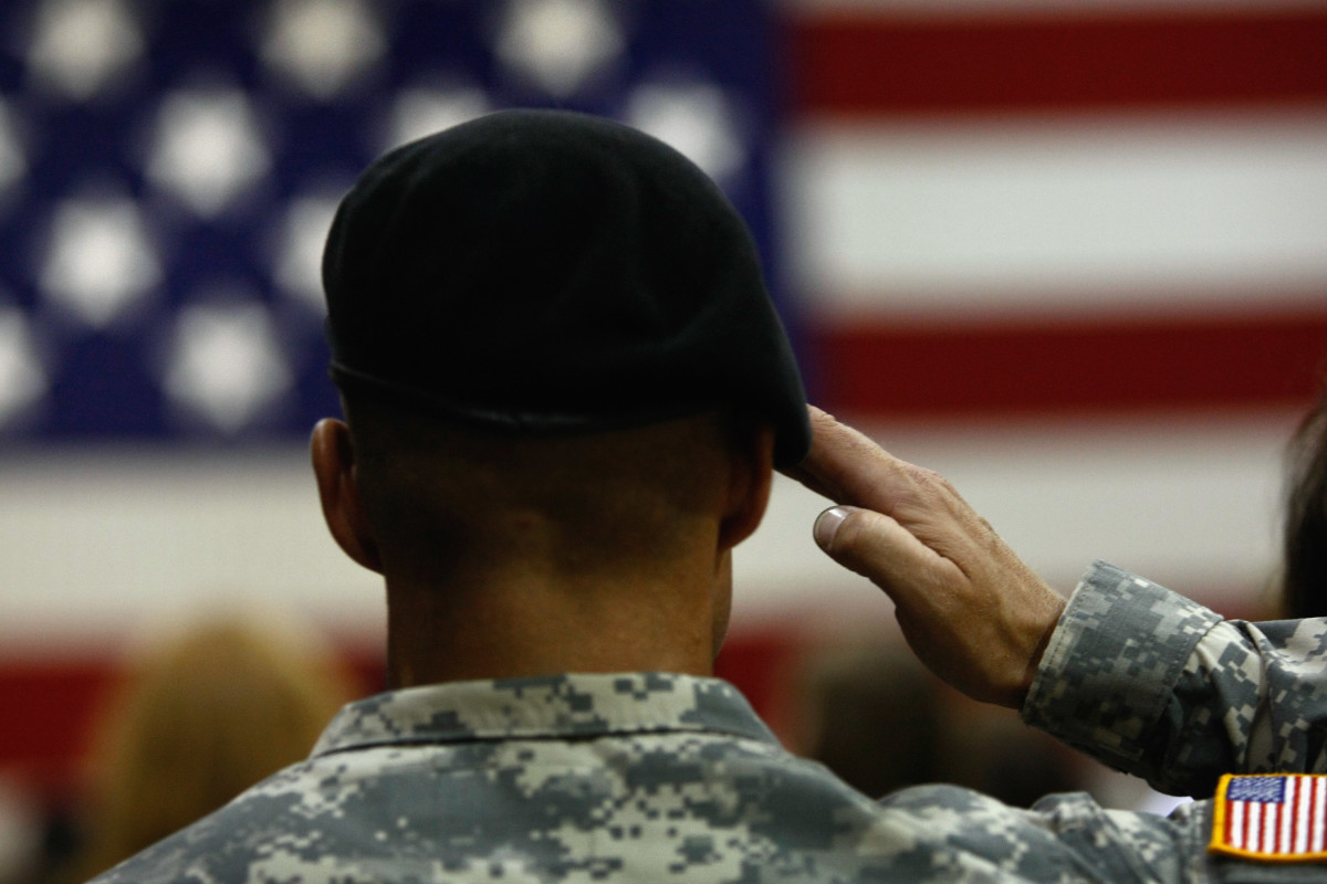 A U.S. Army soldier salutes during the national anthem as soldiers return home from Iraq on August 29th, 2009, in Fort Carson, Colorado.