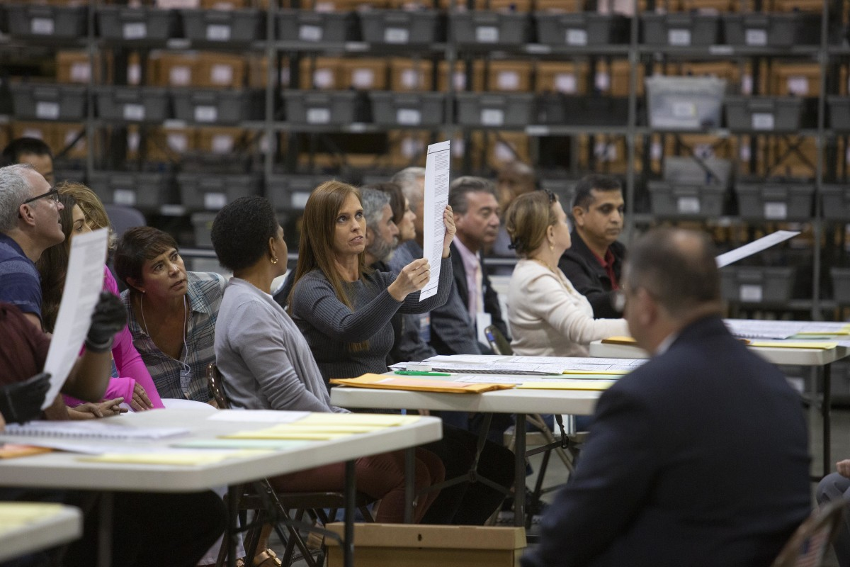 Volunteers look at ballots during a hand recount at the Supervisor of Elections Service Center on November 16th, 2018, in Palm Beach, Florida. After missing a deadline to recount votes for governor, a hand recount has been ordered for the Senate and agriculture commissioner's races.