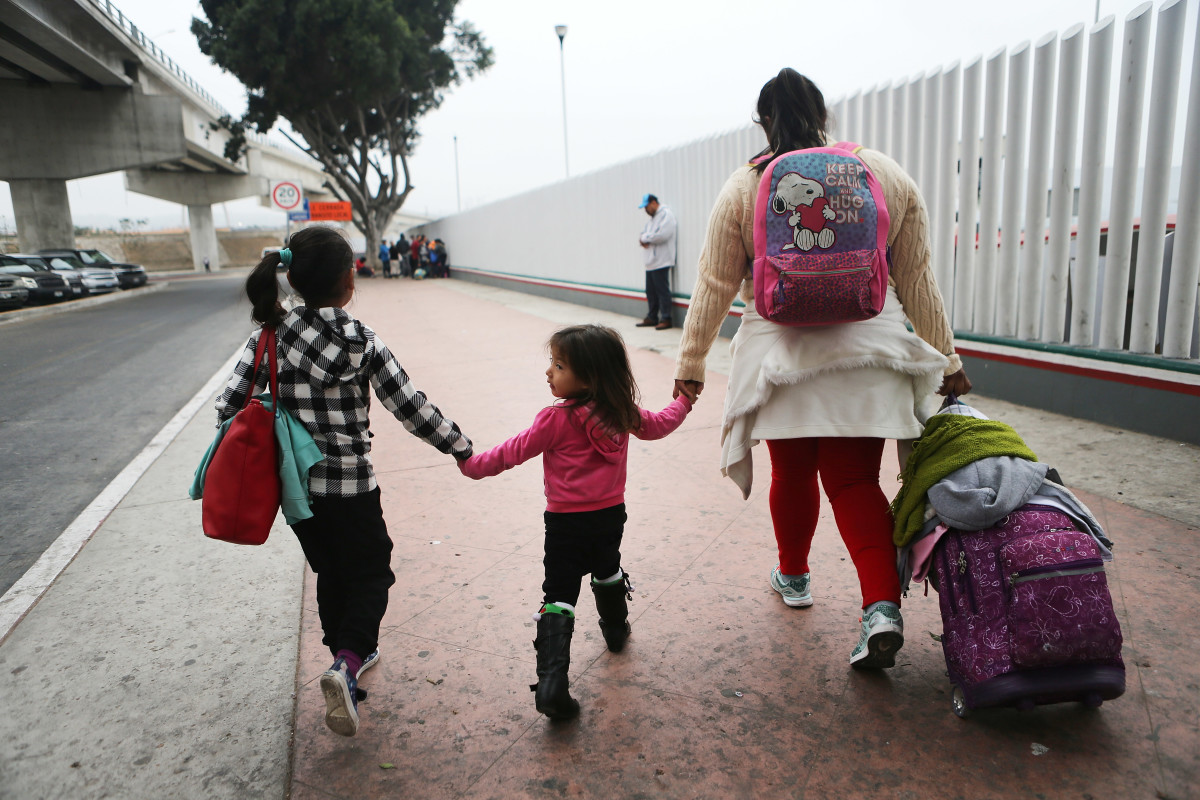 A migrant mother walks with her two daughters on their way to cross the port of entry into the U.S. for their asylum hearing on June 21st, 2018, in Tijuana, Mexico.
