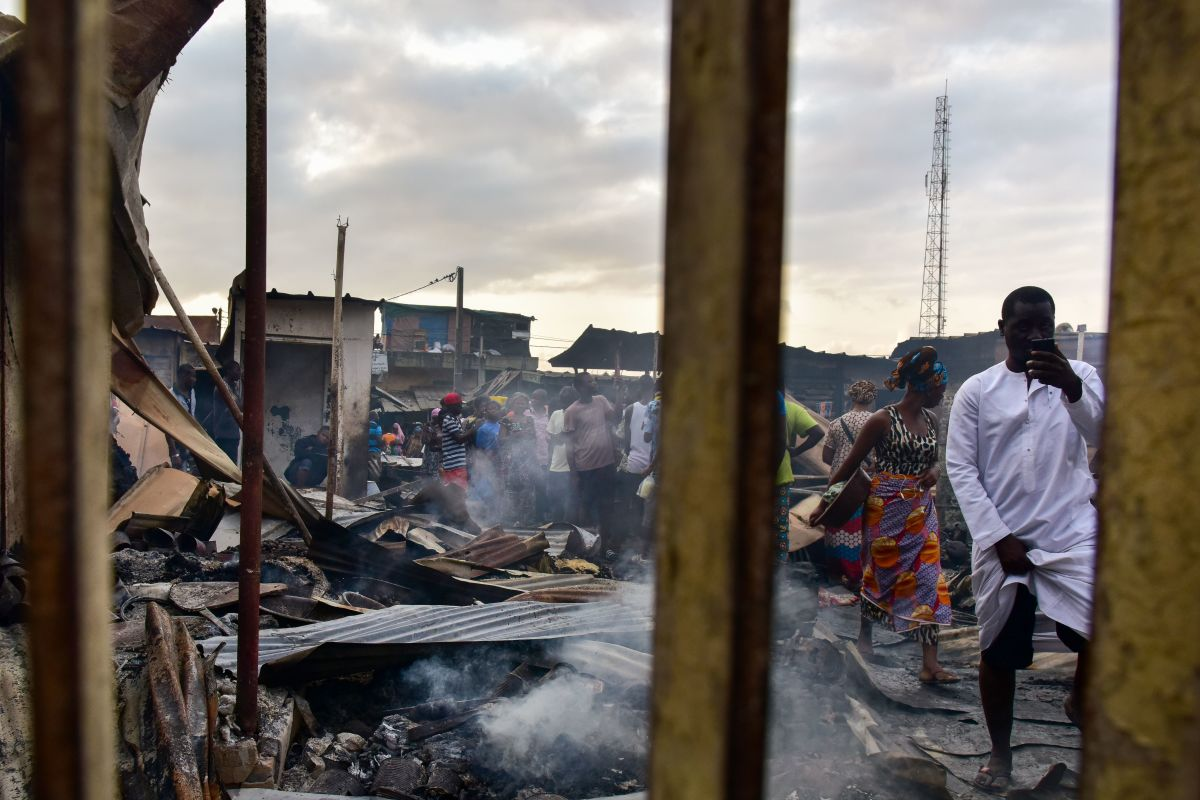 A man takes photos with a mobile phone as sellers walk through debris in a market after a fire devastated the building overnight on September 18th, 2017, in the Abobo neighborhood of Abidjan.