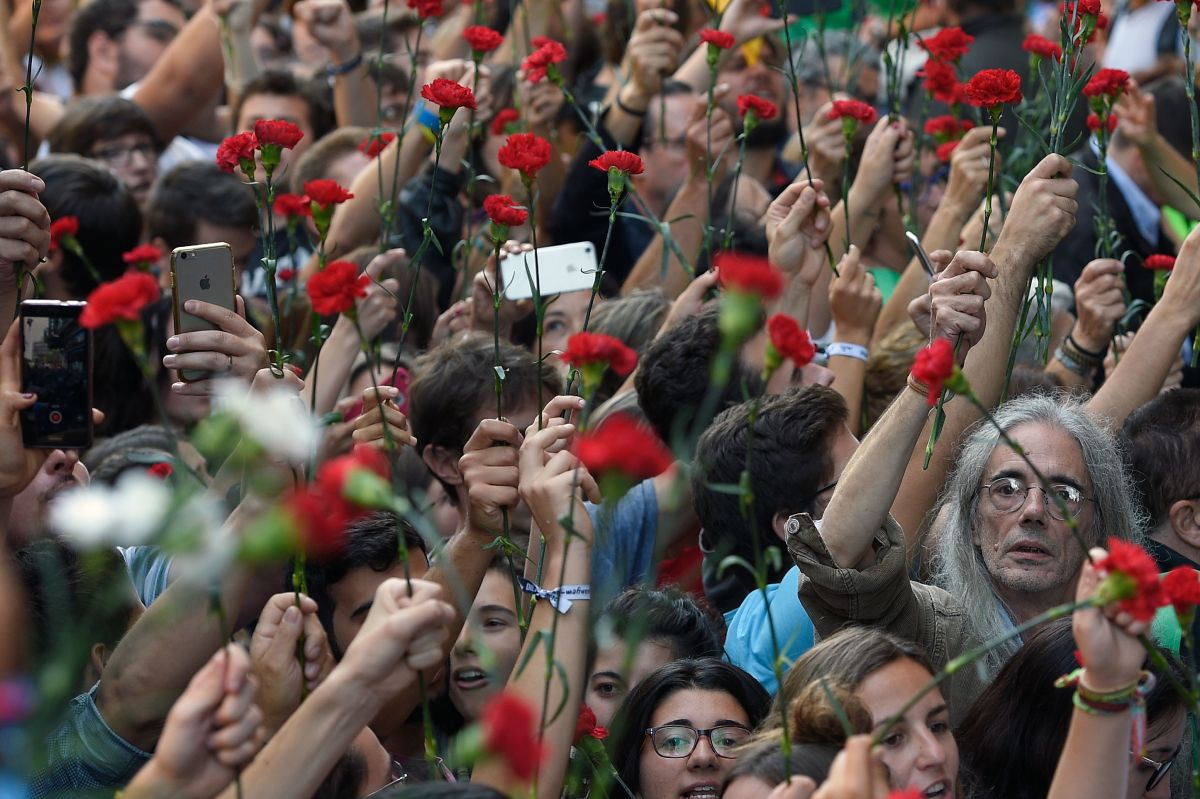 People hold flowers during a protest near the Economy headquarters of Catalonia's regional government in Barcelona on September 20th, 2017.