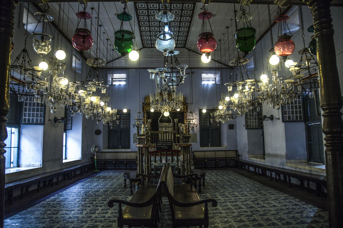 Paradesi Synagogue, quiet after a day of tourists bustling in and out. At the front of the building, a sign asks visitors to remove their shoes before entering. Entering a synagogue barefoot is not a common Jewish practice; it's adopted from Indian traditions.