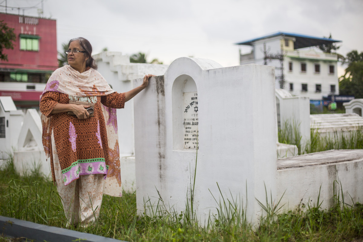 "Ofera Elias, Babu's wife, stands at her grandmother's grave in the Ernakulam Jewish Cemetery. She points out the weeds growing tall around the tombstones. ""No one is taking enough care of this site."" She says that, in the absence of a Jewish community, she and Babu have made their own community of Hindu and Muslim friends."