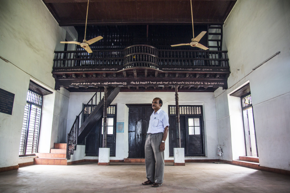 Karma Chandran stands in the empty Mala Synagogue, 50 kilometers from Cochin. He is fighting to preserve the Mala Synagogue and Jewish cemetery, two sites that have been heavily neglected for decades. When the Mala Jewish community migrated to Israel in 1955, they made a written agreement with the local government to protect the sites, but, in 2012, the local government made plans to build a stadium on cemetery land anyway. Now, the blue-and-red stadium looms over the remaining tombstones, the stadium left empty and half-constructed because of ongoing court cases between the government and the departed Jewish community.