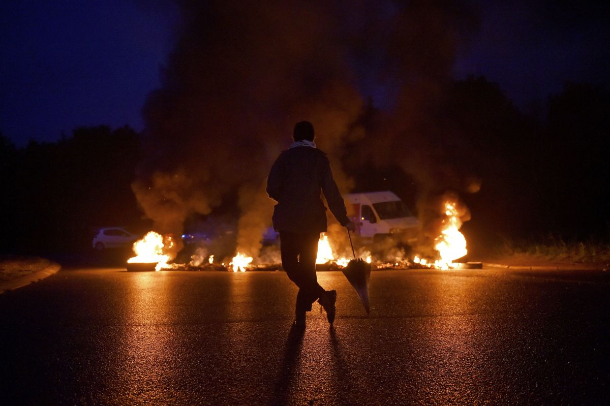 A protester watches a burning traffic circle while union trade members block trucks on September 25th, 2017, in Donges, France, to protest the government's labor law.