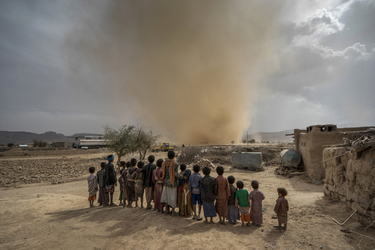 In April, children watch a dust devil whip up sand as it travels across the desert landscape near the town of Huth, about 50 miles north of Yemen's capital.