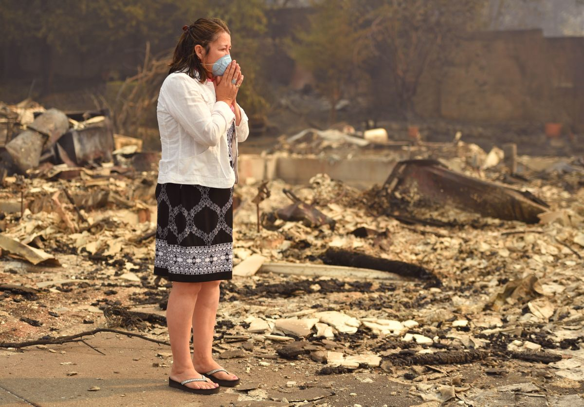 A woman looks at the wreckage of her burned home in Santa Rosa, California, on October 10th, 2017. Firefighters were battling 17 large wildfires, which have left at least 13 people dead, thousands homeless, and ravaged the state's wine country.