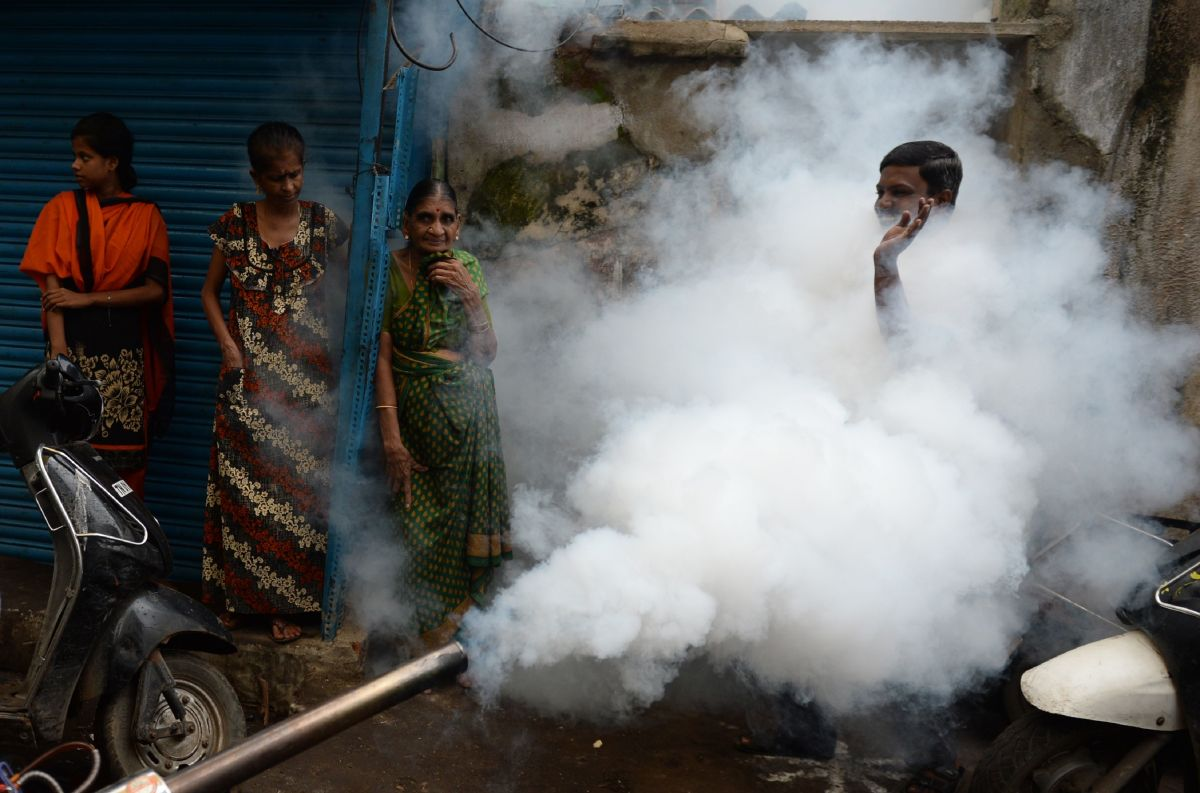 A man gestures while a municipal worker fumigates the area to prevent mosquitos from breeding in Chennai, India, on October 12th, 2017. Several cases of the mosquito-borne virus dengue have been reported from the state capital and adjoining areas, officials said, with 27 disease-related deaths reported in Tamil Nadu state.