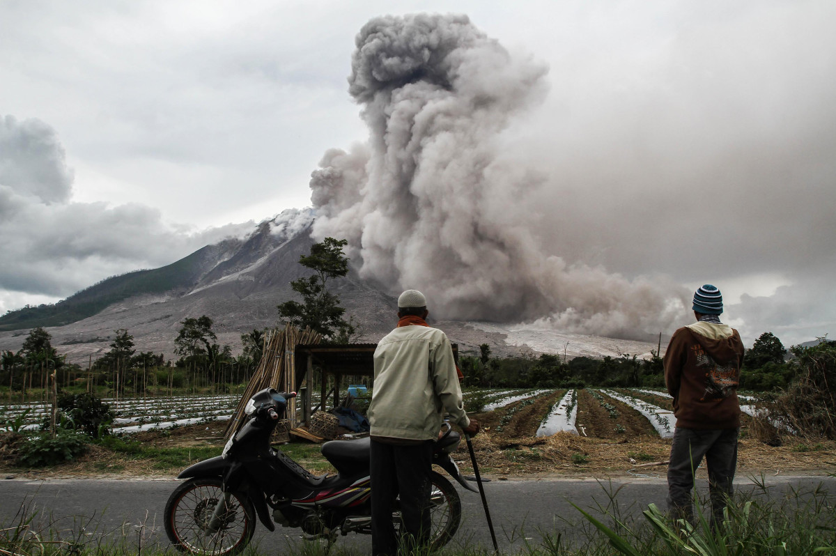 Indonesian villagers watch as Mount Sinabung volcano erupts in Karo, North Sumatra, on October 24th, 2017. Sinabung roared back to life in 2010 for the first time in 400 years and has remained highly active since.