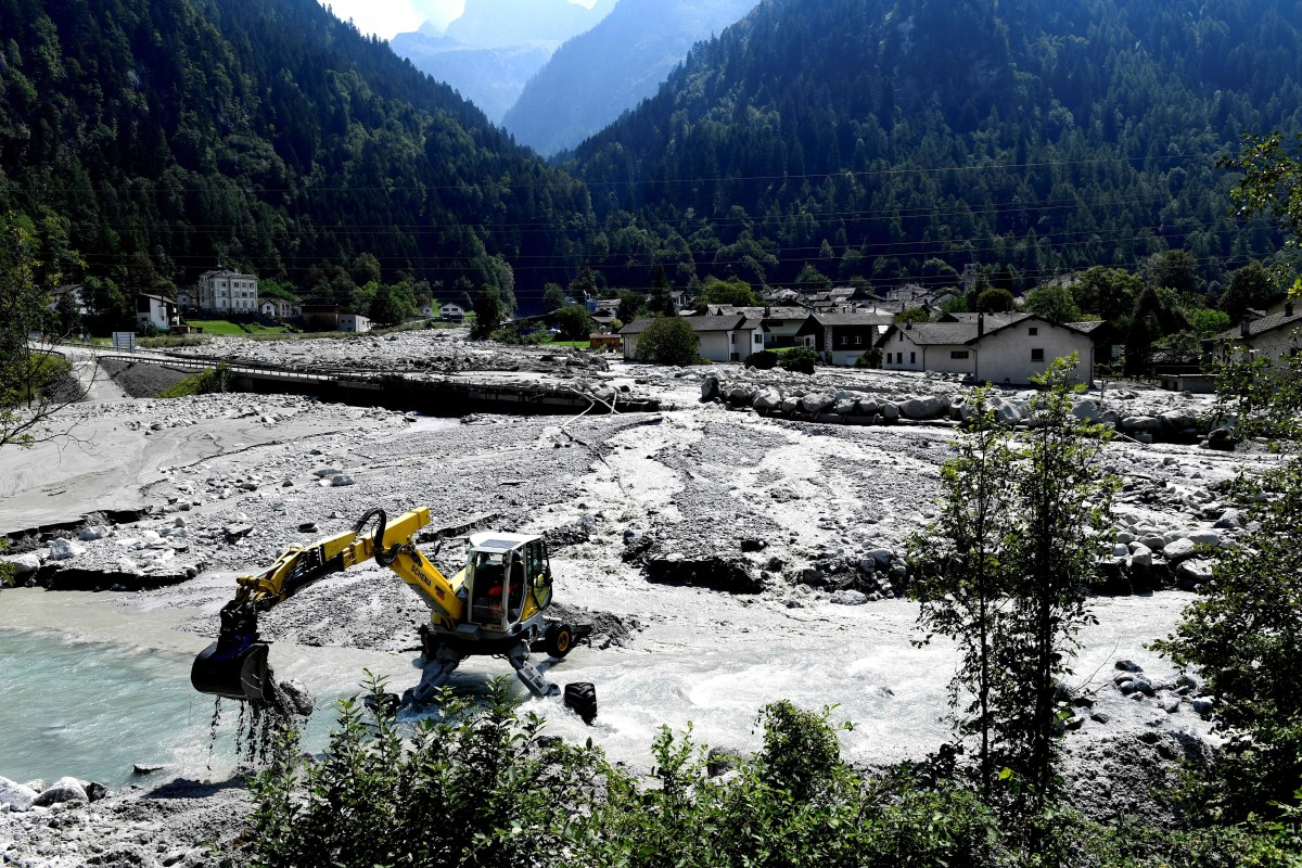 A digger clears rocks and debris on the outskirts of the village of Bondo in the Swiss Alps following a landslide on August 25th, 2017.