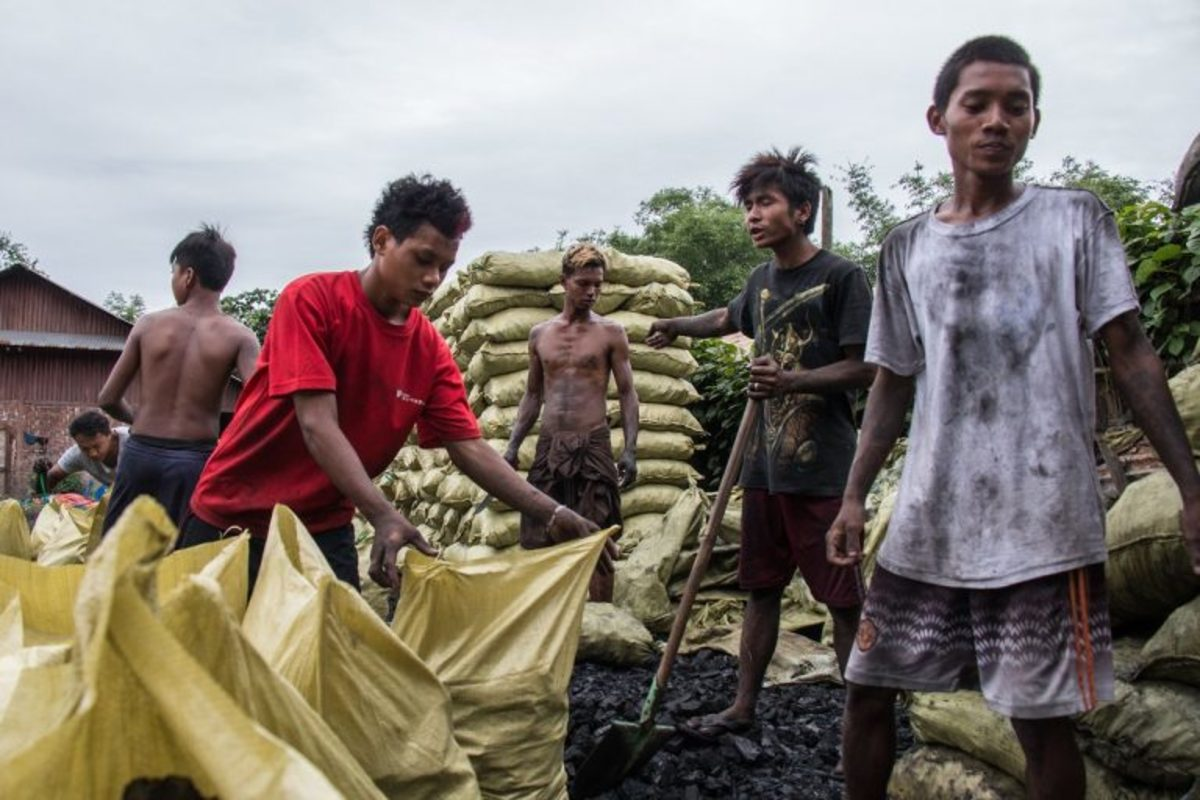 Workers manage hundreds of charcoal bags stored in a lot in Bhamo, Myanmar, before they're loaded onto trucks and bound for China.